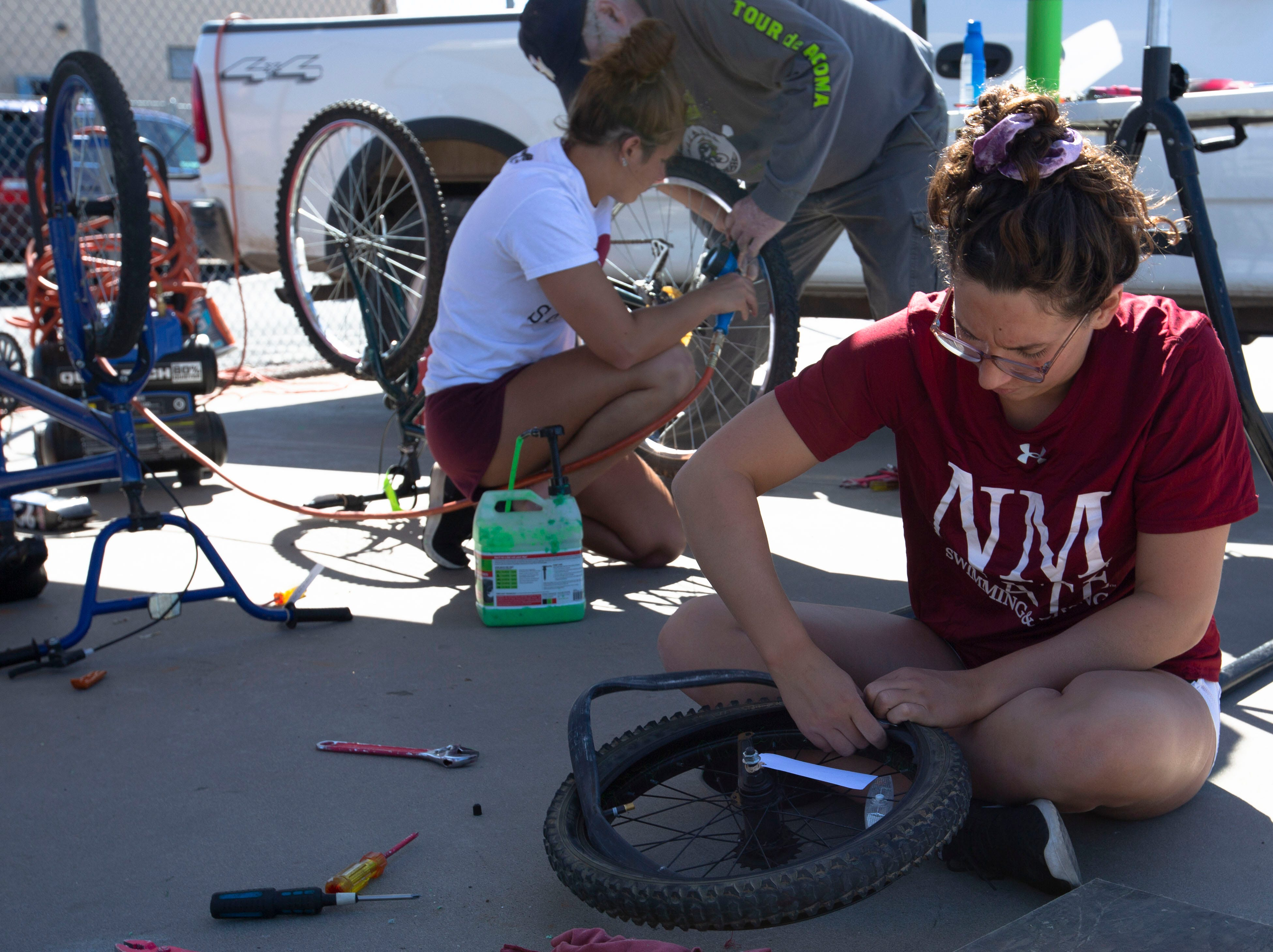 A member of the New Mexico State swim team, Moana Houde-Camirand  fixes a bike tire on Saturday, April 27, 2019. Houde-Camirand said she was volunteering at the Family Bike Fiesta to give back to the community.