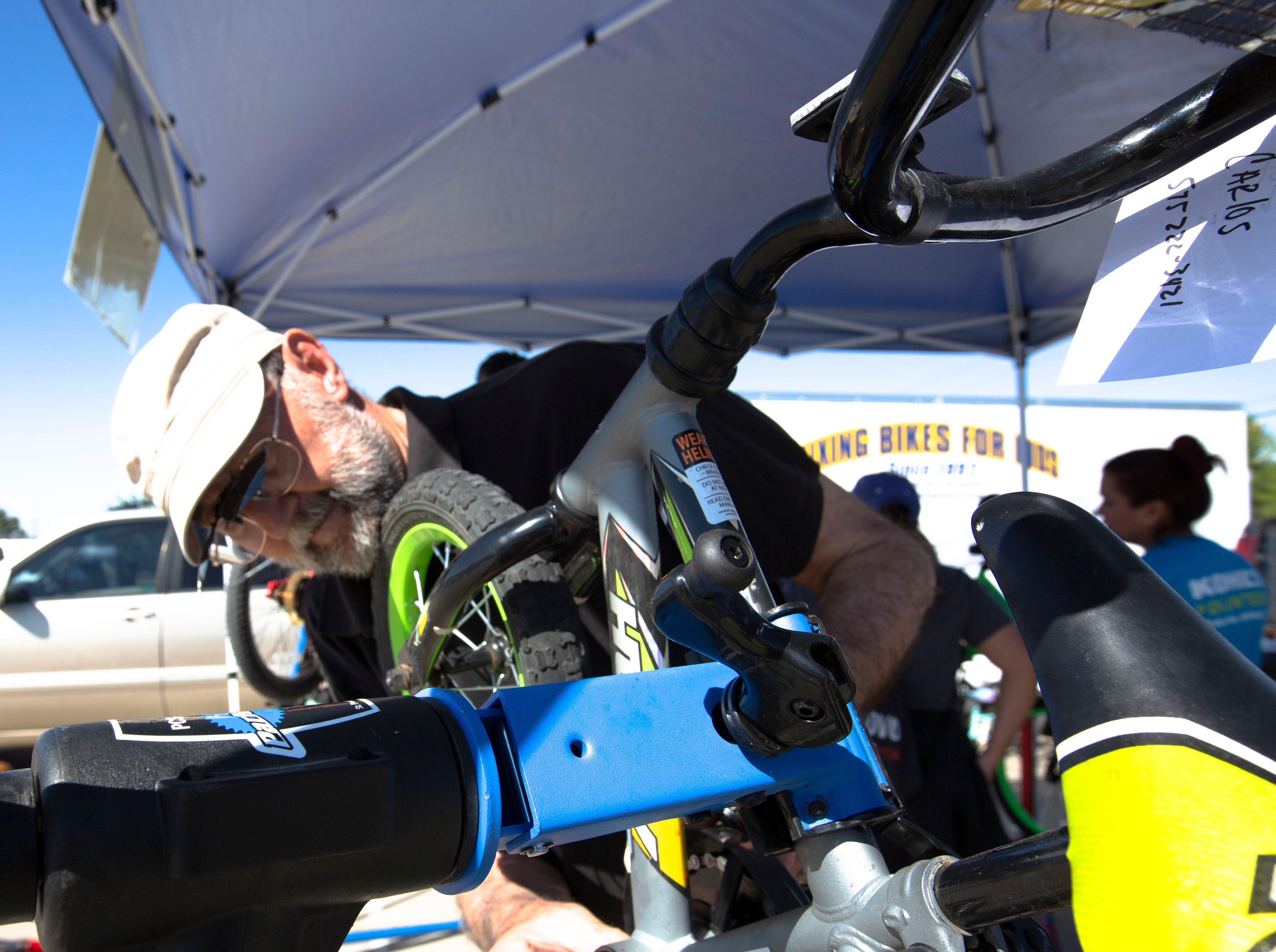 Doug Henson works to repair a child's bike Saturday, April 27, 2019, at the Family Bike Fiesta in Las Cruces.