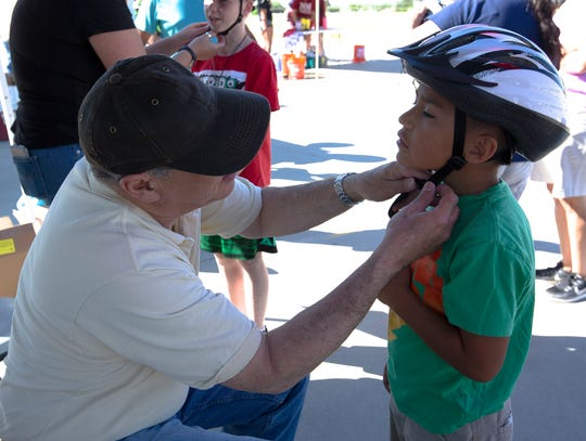 Angel Olivas, 8, is fitted with a brand new bike helmet Saturday, April 27, 2019, at the annual Family Bike Fiesta at Lynn Middle School.