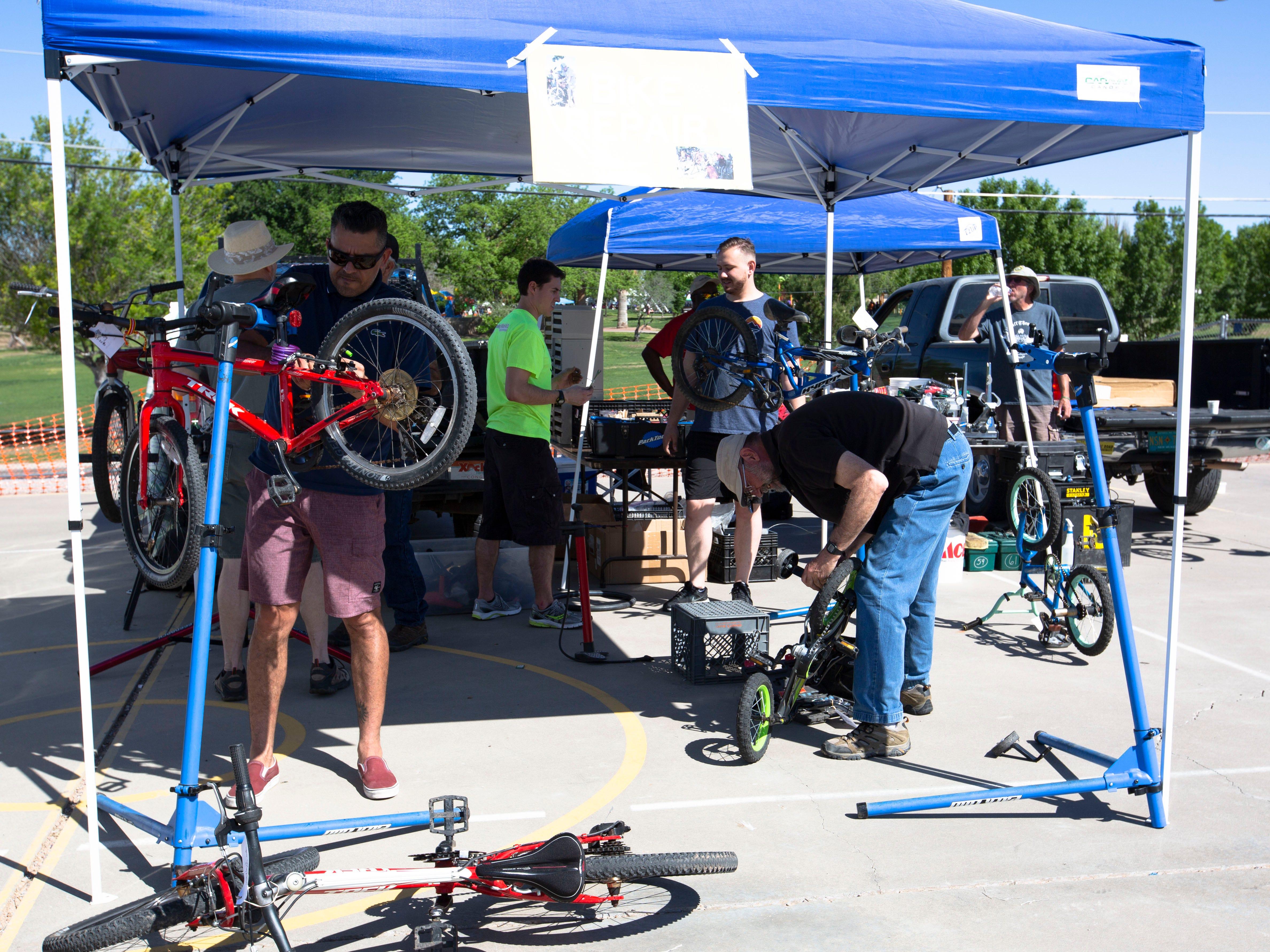 Volunteers work to repair children's bikes Saturday, April 27, 2019, at the Family Bike Fiesta at Lynn Middle School in Las Cruces.