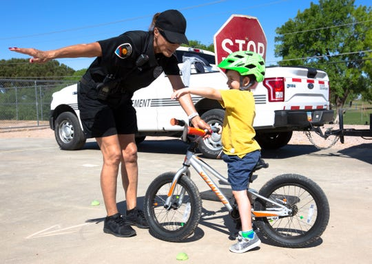 Alec Davis, 4, learns the rules of the road  from Mary Ann Teries, a code enforcement officer with the Las Cruces Police Department, during the 10th annual Family Bike Fiesta Saturday, April 27, 2019, at Lynn Middle School.