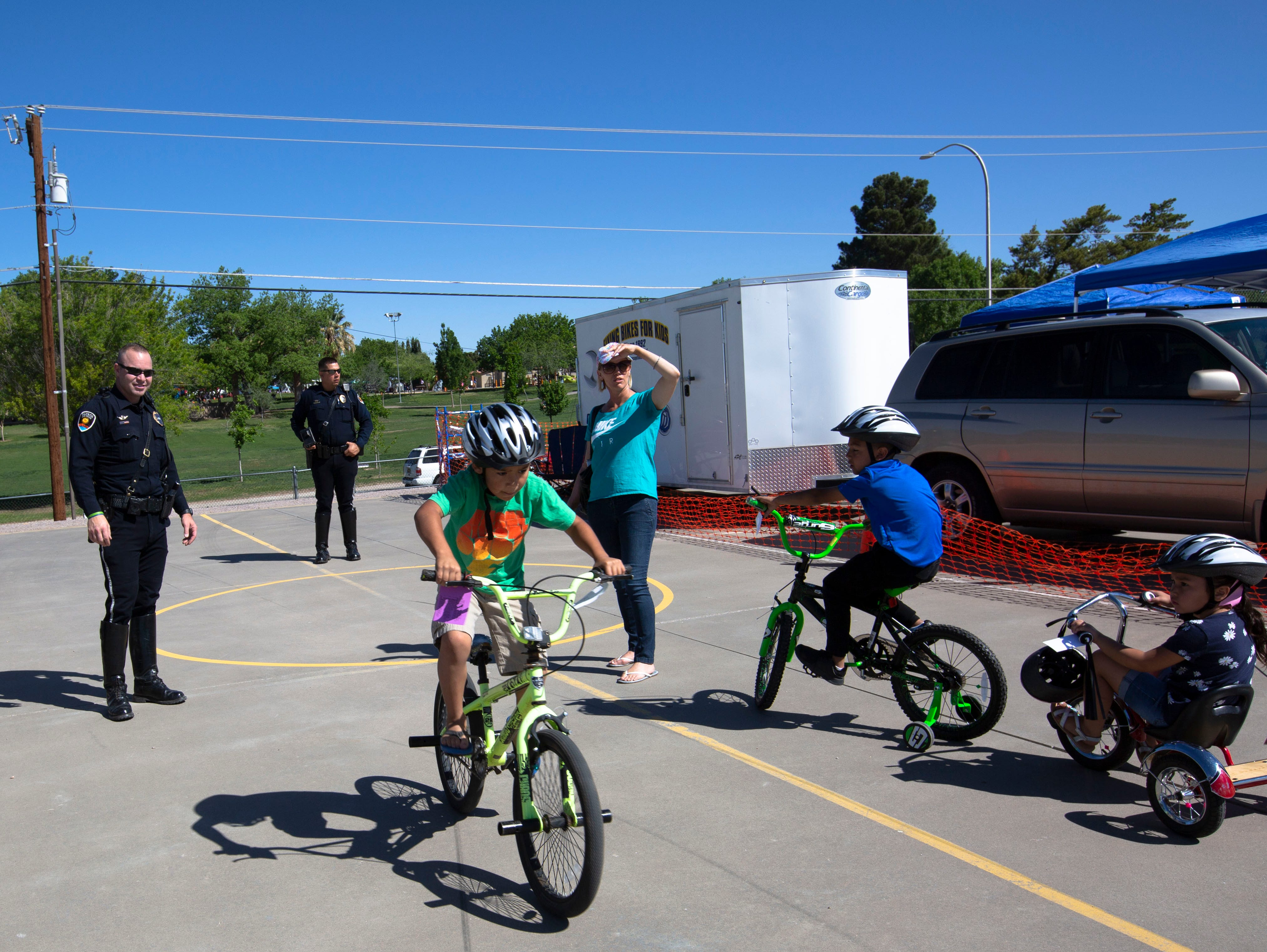 """Police officers with the Las Cruces Police Department """"clock"""" how fast Family Bike Fiesta participants can go on their bikes at the Family Bike Fiesta Saturday, April 29, 2019."""