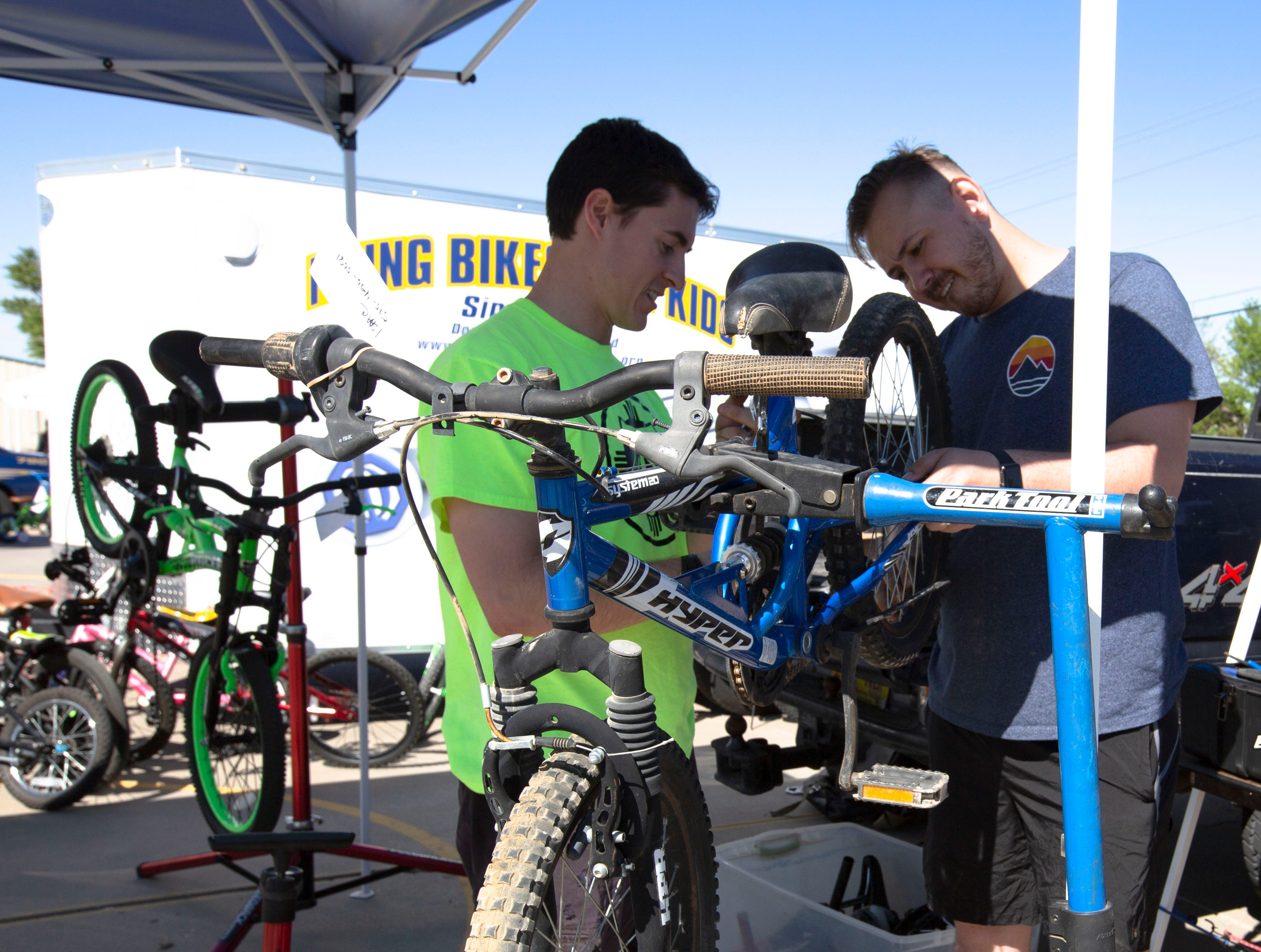 Volunteers Wesley Goodrich and Tyler Christensen, fix a child's bike on Saturday, April 27, 2019, at the Family Bike Fiesta in Las Cruces.