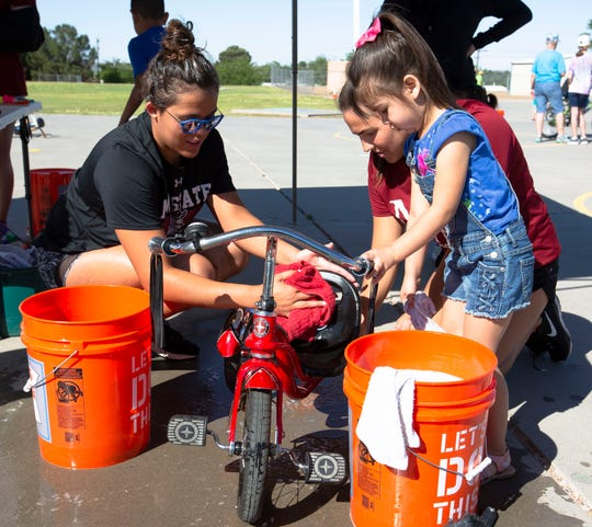 Natalia Villa and Lauren Hemourrow help Priscilla Para, 4, wash her bike Saturday, April 27, 2019, at the 10th annual Family Bike Fiesta.