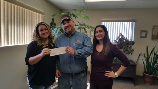 McChristie Curry of White Sands Construction Inc. hands a check to Zygmunt Kruszewski (Senior Crewman) and Rosalia Pizano (Senior Customer Service Representative) of New Mexico Gas Company, to help pay the utility bill for one of Alamogordo's community members in need.