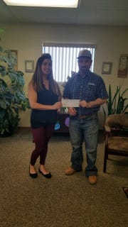 Eugene Varbel (project manager) of White Sands Construction Inc. hands a check to Rosalia Pizano (Senior Customer Service Representative) of New Mexico Gas Company, to help pay the utility bill for one of Alamogordo's community member in need. of donations.