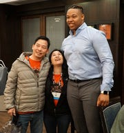 """6'7"""", 312 lbs. NFL-prospective Michael Jordan poses with the not-so-large Mike and Dee Nguyen on April 26 at the Canton Hampton Inn. The Nguyens were in town for the high school robotics competition and wanted to have a photo with the NFL prospect."""