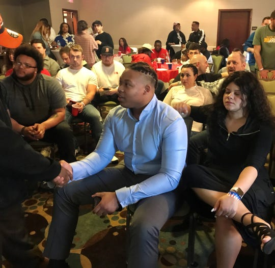 Former Plymouth offensive lineman Michael Jordan greets a friend at his NFL Draft party Friday night in Canton.