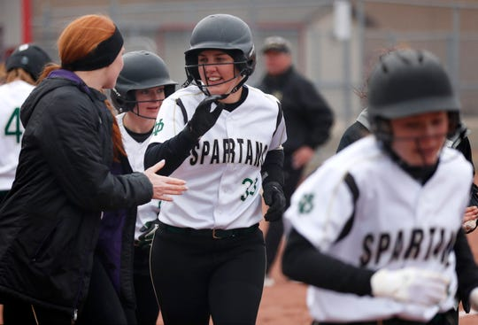 Oshkosh North's Libby Neveau celebrates with teammates during a game against Appleton East on April 4 in Appleton.