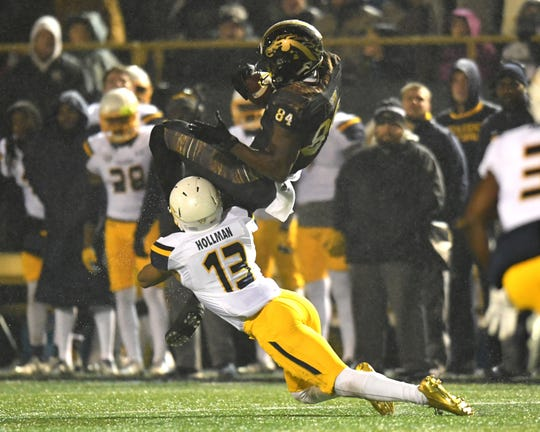 Toledo cornerback Ka'dar Hollman tackles Western Michigan wide receiver Corey Davis during a game in 2016.