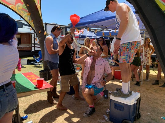 Drinking games are among the many activities that take place in the campgrounds at the Stagecoach country music festival in Indio, Calif., April 26, 2019