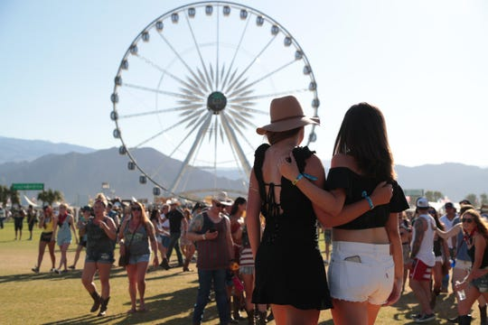 """Festivalgoers line up to take photos under the """"Stagecoach"""" sign at the Stagecoach country music festival, Indio, Calif., April 26, 2019."""