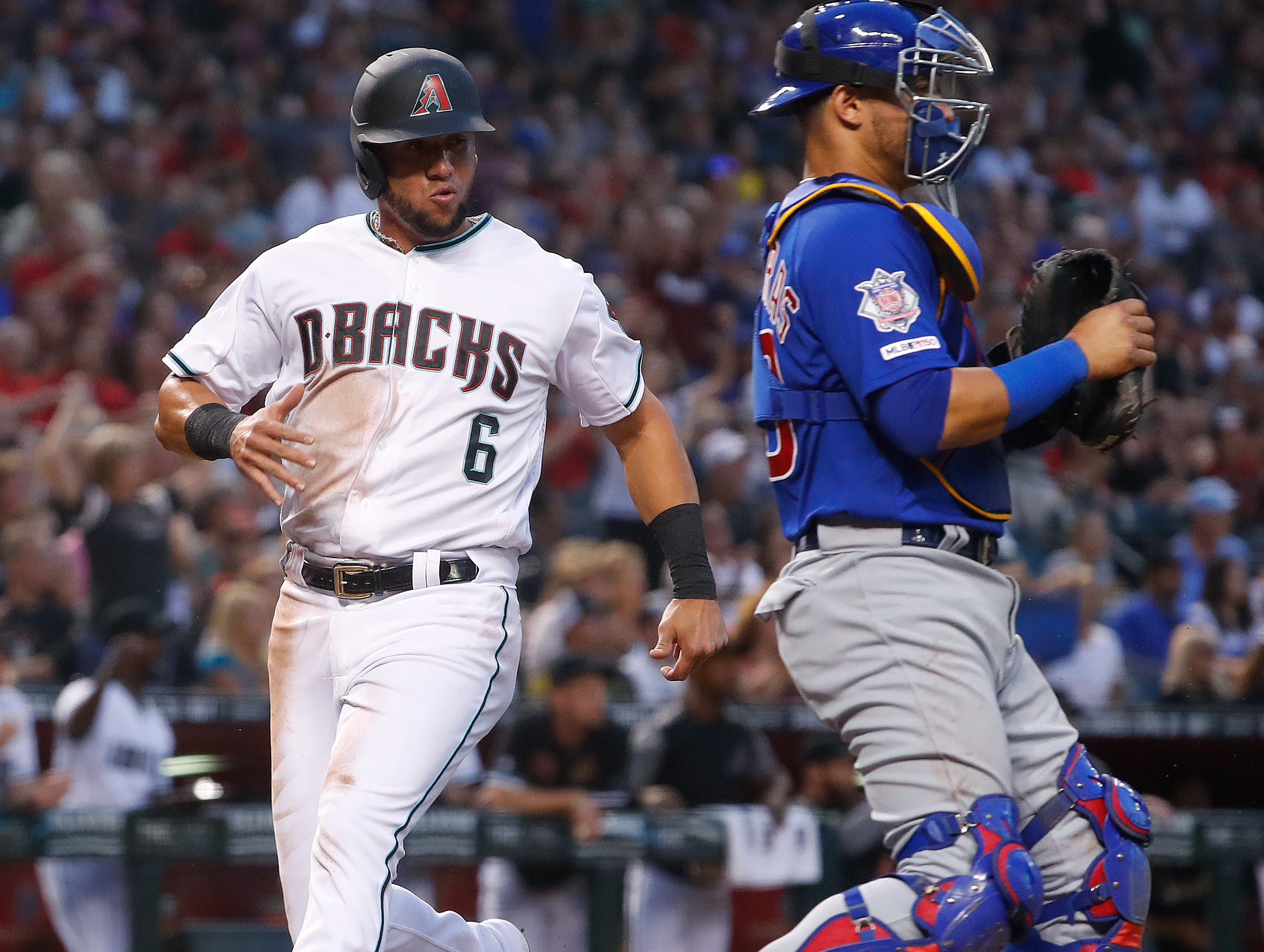 Diamondbacks' David Peralta (6) steps on home plate past Cubs' Willson Contreras (40) scoring during the first inning at Chase Field in Phoenix, Ariz. on April 26, 2019.