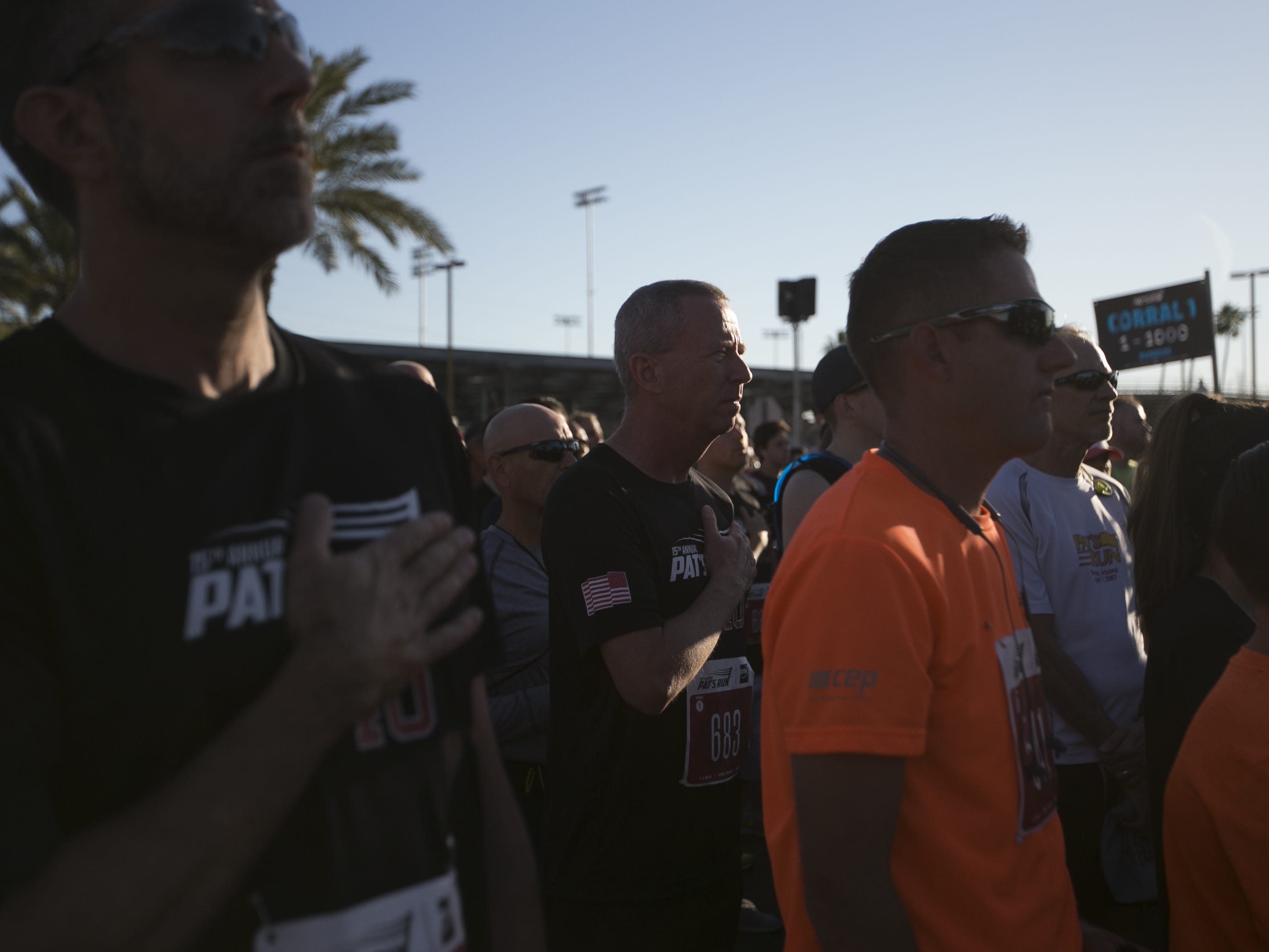 Runners cross their hands over their hearts as the national anthem is performed at Pat's Run 2019 in Tempe on April 27, 2019.