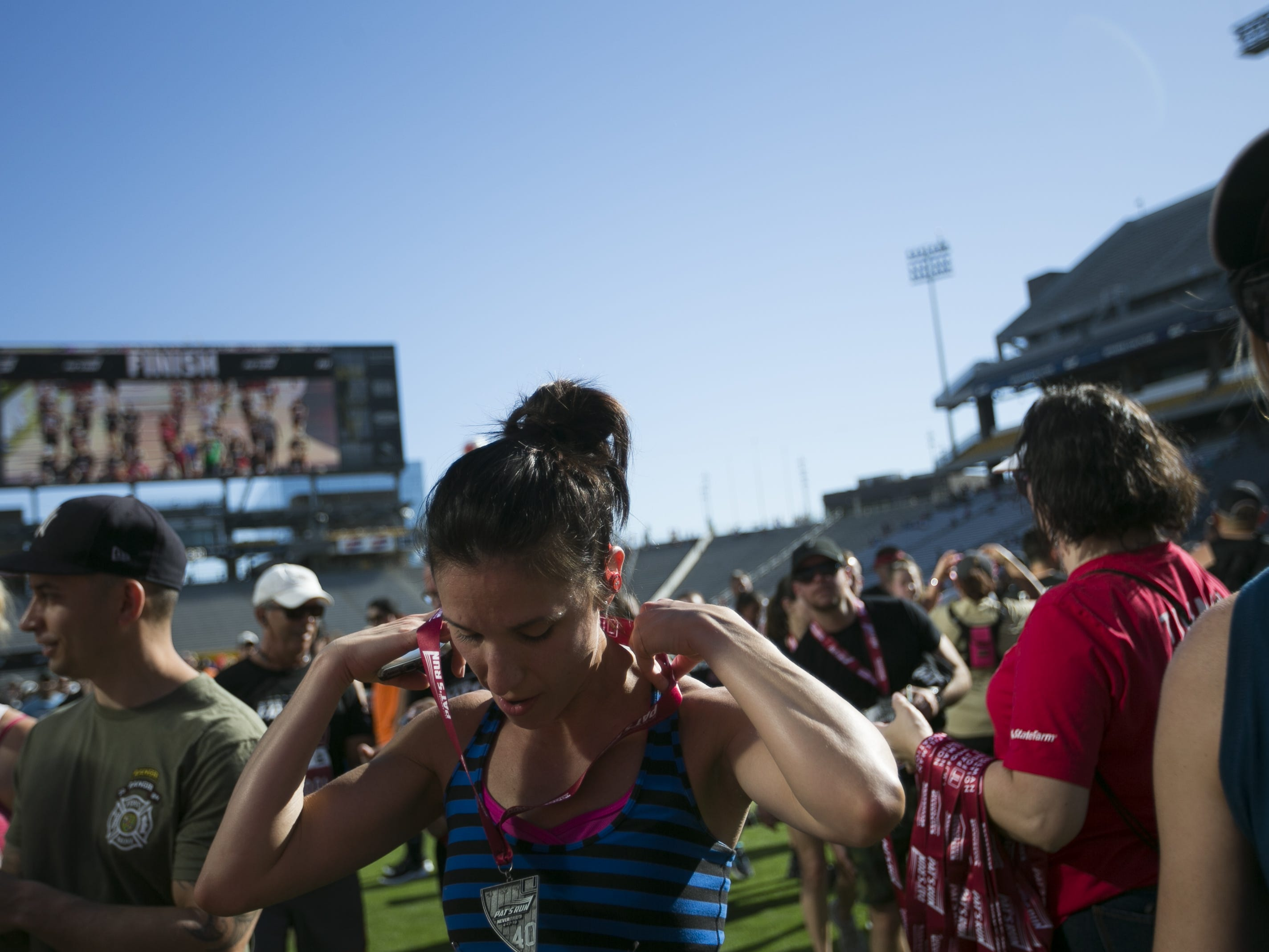 Christina Conte places a medal over her neck after finishing Pat's Run 2019 in Tempe on April 27, 2019.