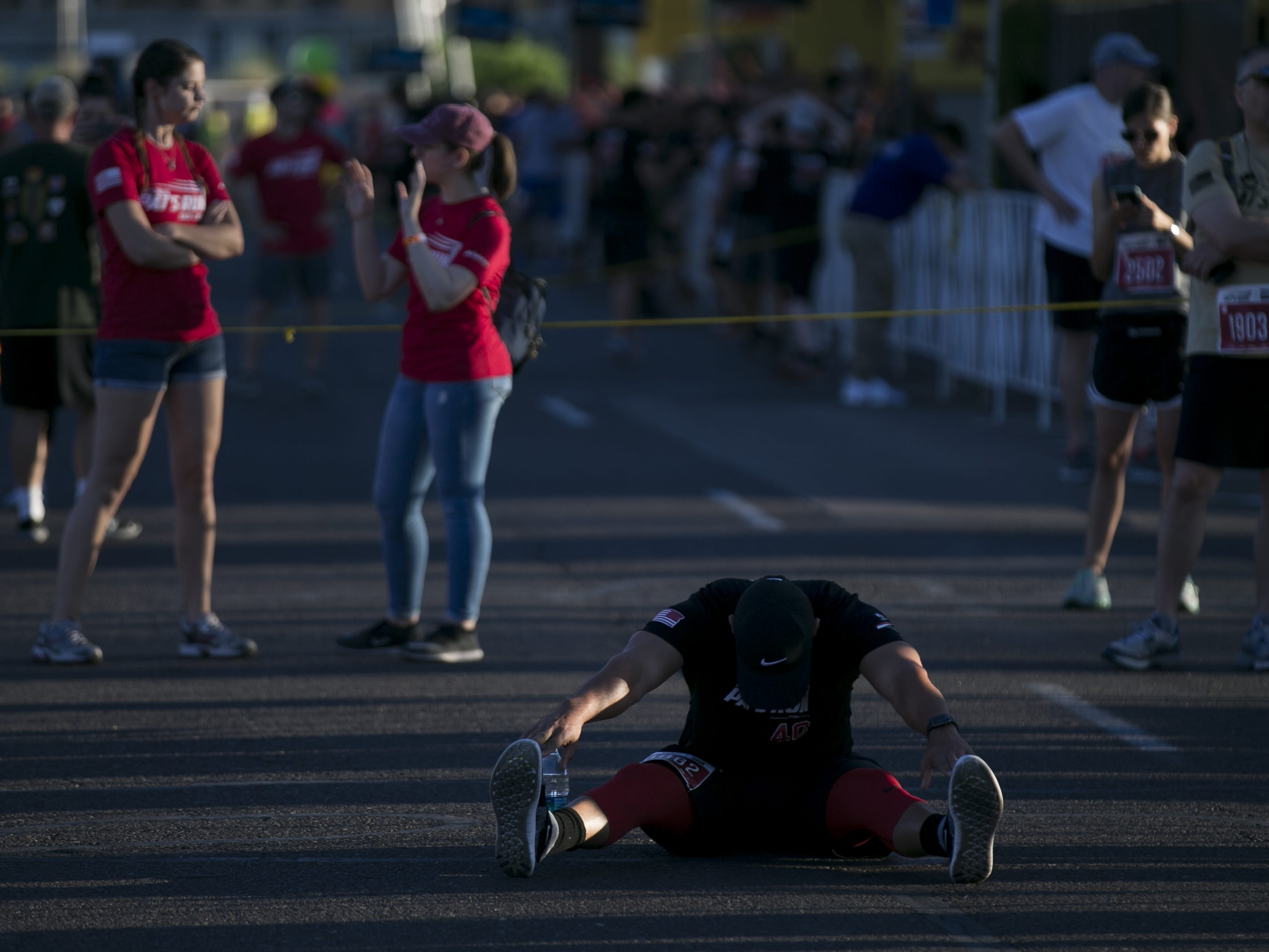 Runners stretch before participating in Pat's Run 2019 in Tempe on April 27, 2019.