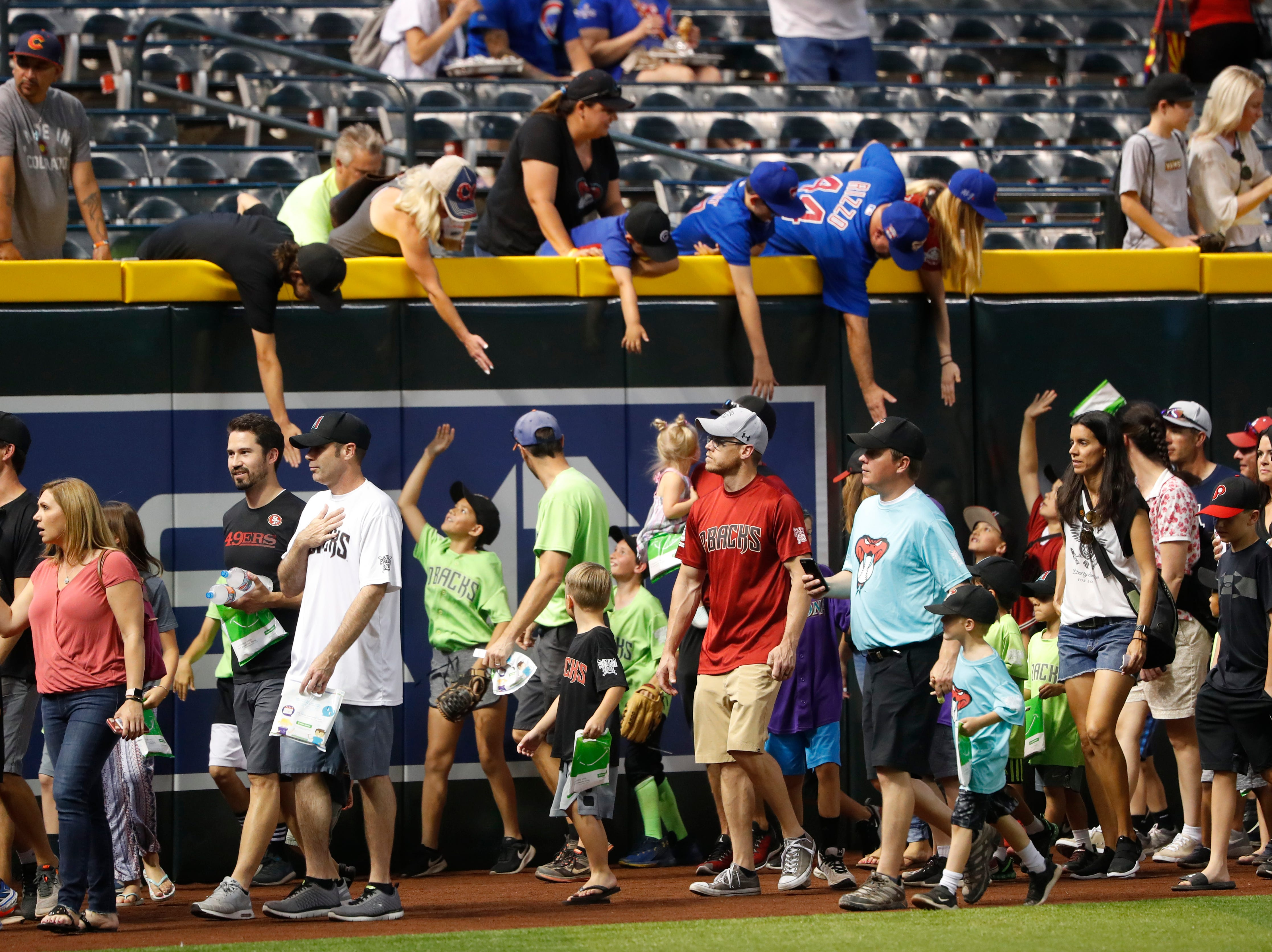 Fans make their way around the outfield dirt during the Arizona All-Stars Parade before a Cubs vs. Diamondbacks game at Chase Field in Phoenix, Ariz. on April 26, 2019.