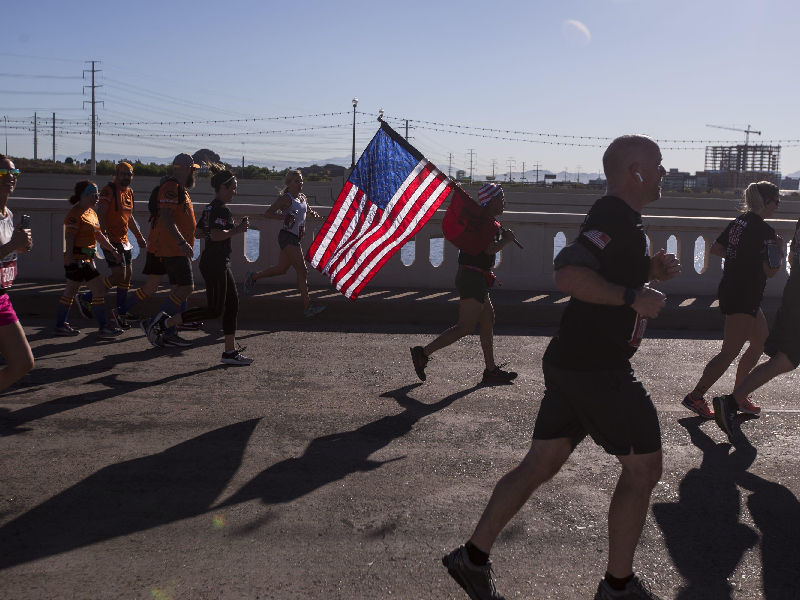 Participants run across the Mill Avenue bridge during the 15th Annual Pat's Run on Saturday, April 27, 2019, in Tempe, Ariz.