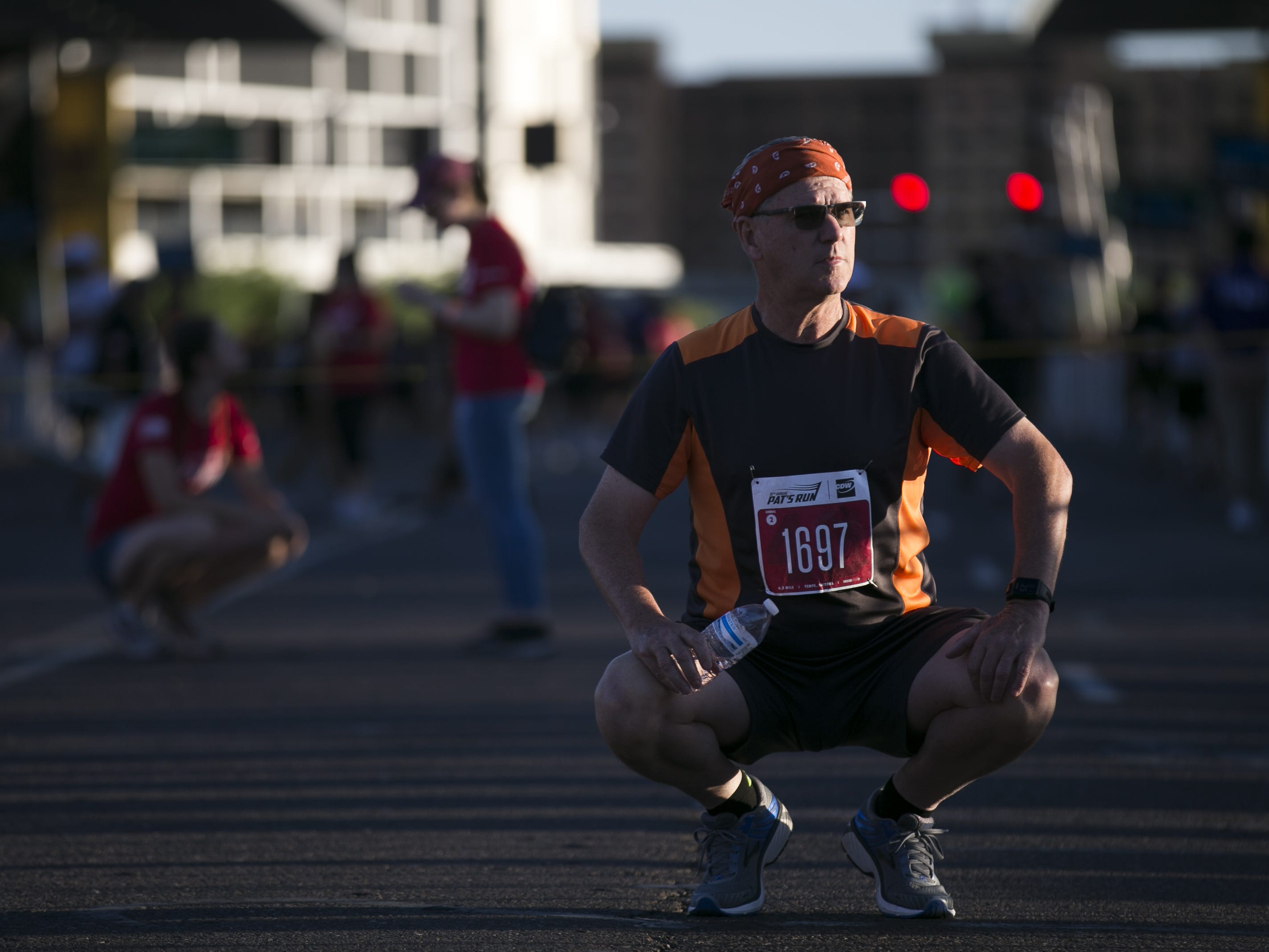 Tom Salesman stretches before running in Pat's Run 2019 in Tempe on April 27, 2019.