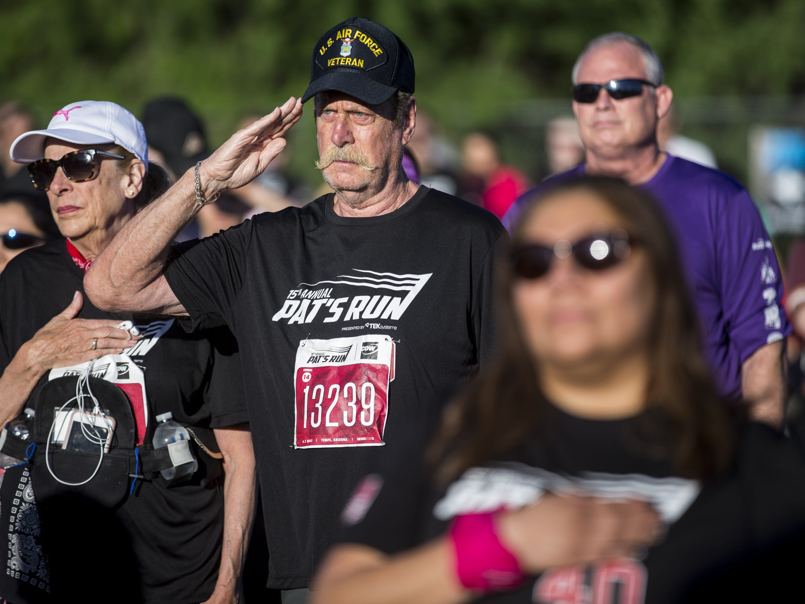 Participants stand during the national anthem before the 15th Annual Pat's Run on Saturday, April 27, 2019, in Tempe, Ariz.
