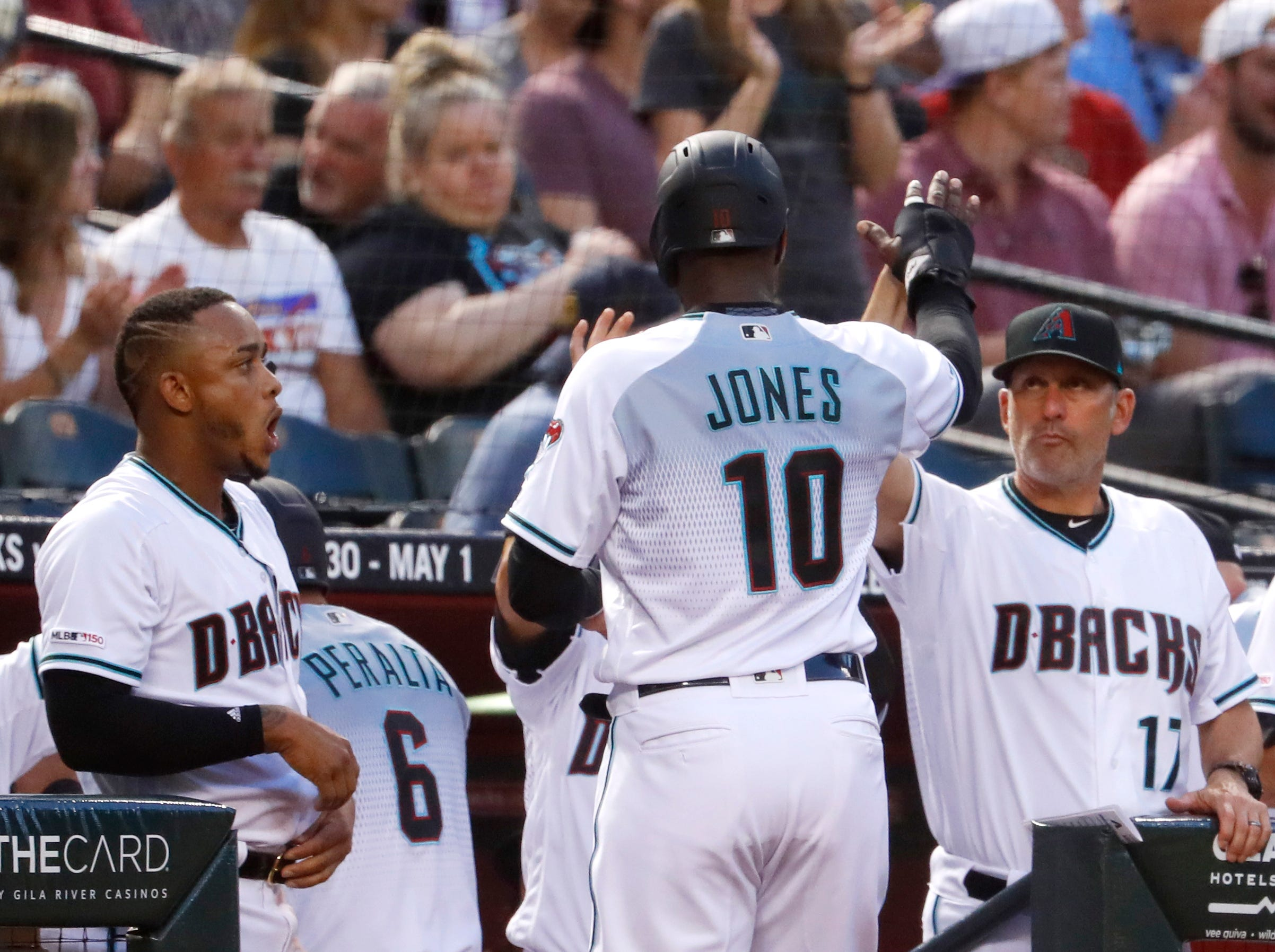Diamondbacks' manager Torey Lovullo (R) high-fives Adam Jones (10) after Jones scored during the first inning at Chase Field in Phoenix, Ariz. on April 26, 2019.