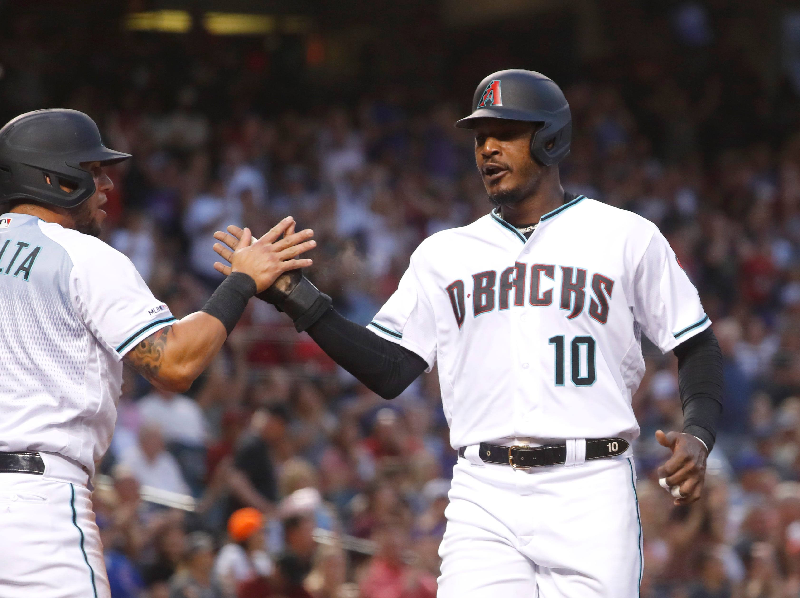 Diamondbacks' Adam Jones (10) high-fives David Peralta (6) after they scored against the Cubs during the first inning at Chase Field in Phoenix, Ariz. on April 26, 2019.