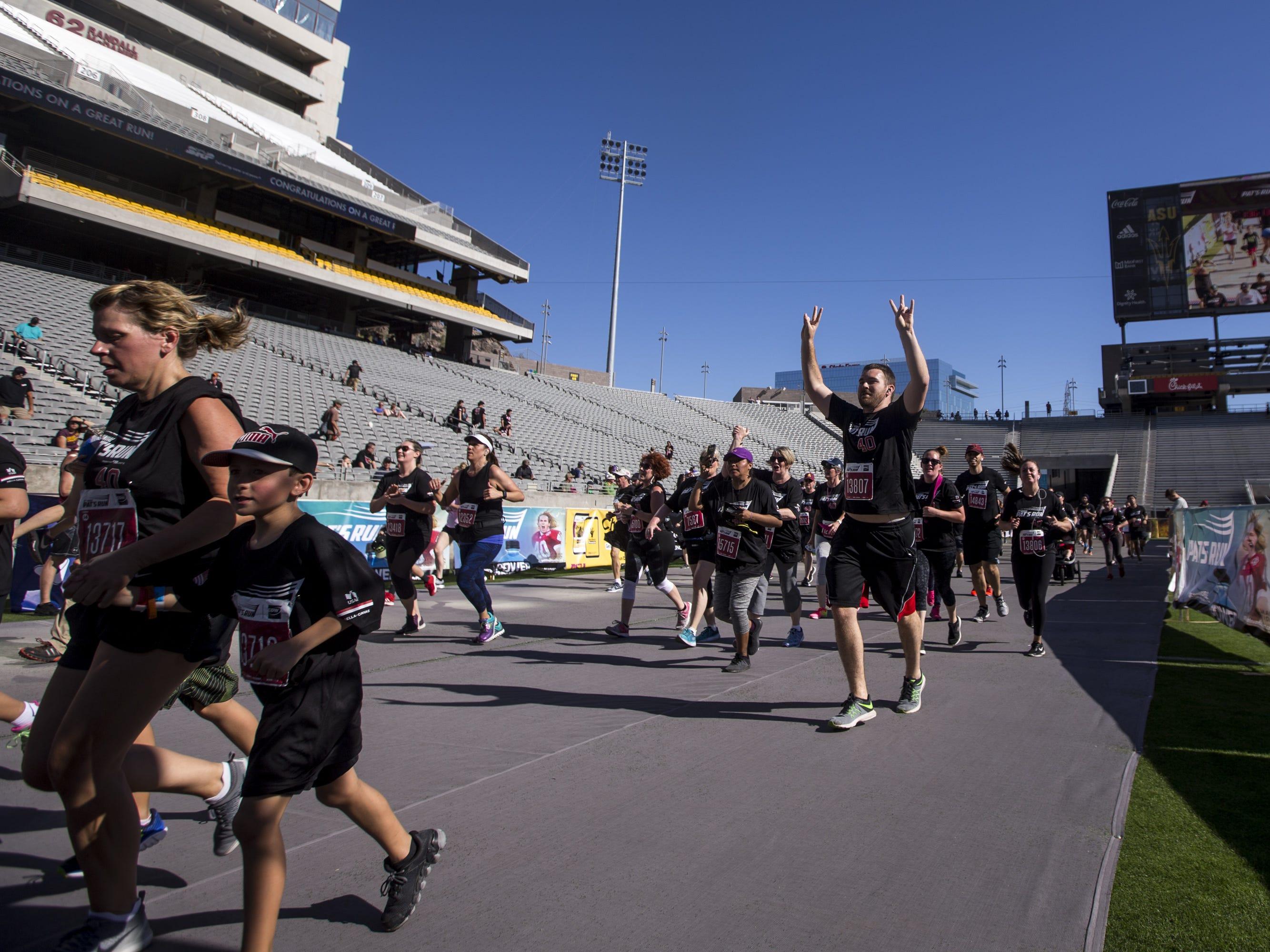 Participants run toward the finish line at Sun Devil Stadium during the 15th Annual Pat's Run on Saturday, April 27, 2019, in Tempe, Ariz.