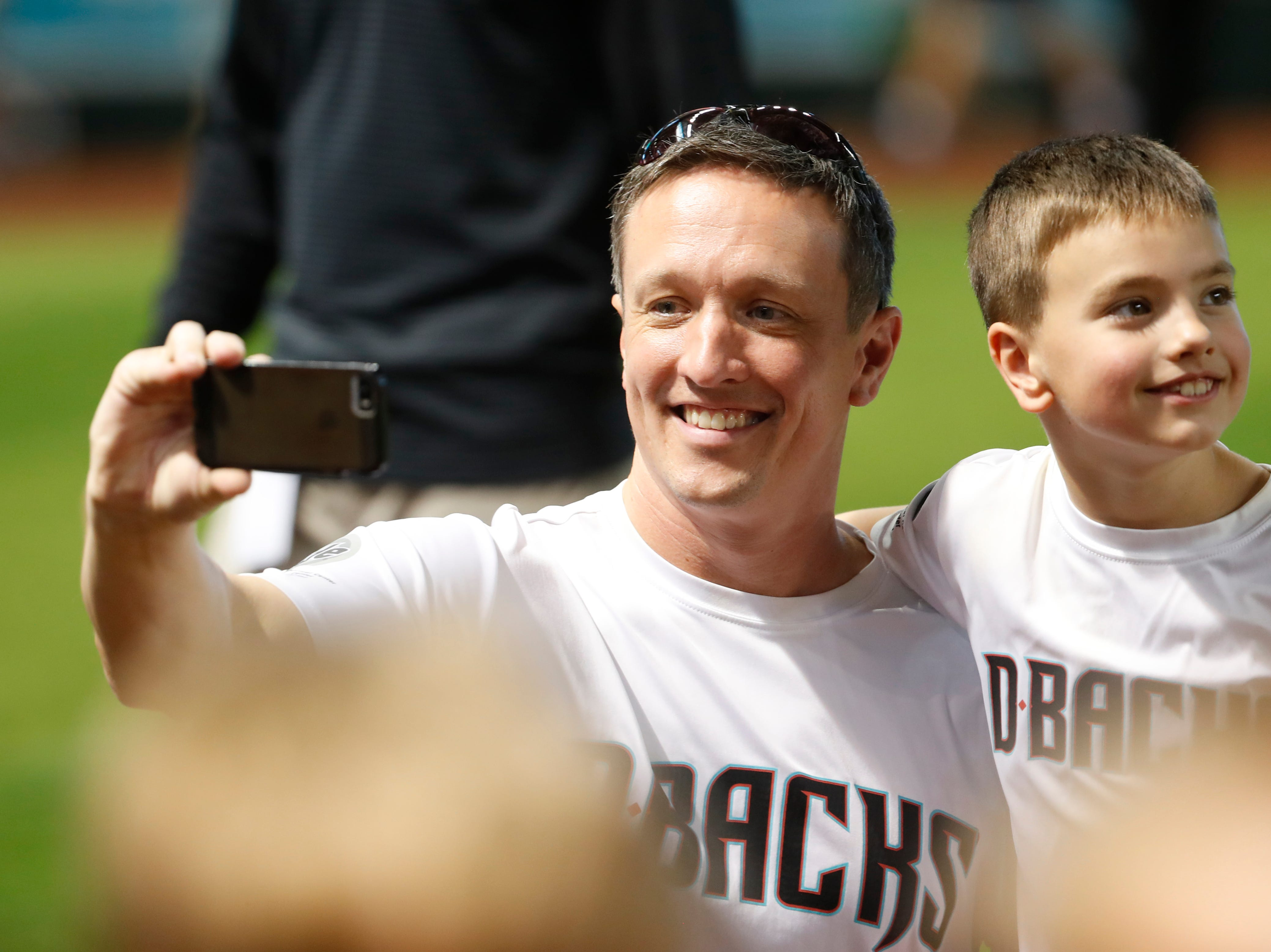 Fans take selfies on the field during the Arizona All-Stars Parade before a Cubs vs. Diamondbacks game at Chase Field in Phoenix, Ariz. on April 26, 2019.