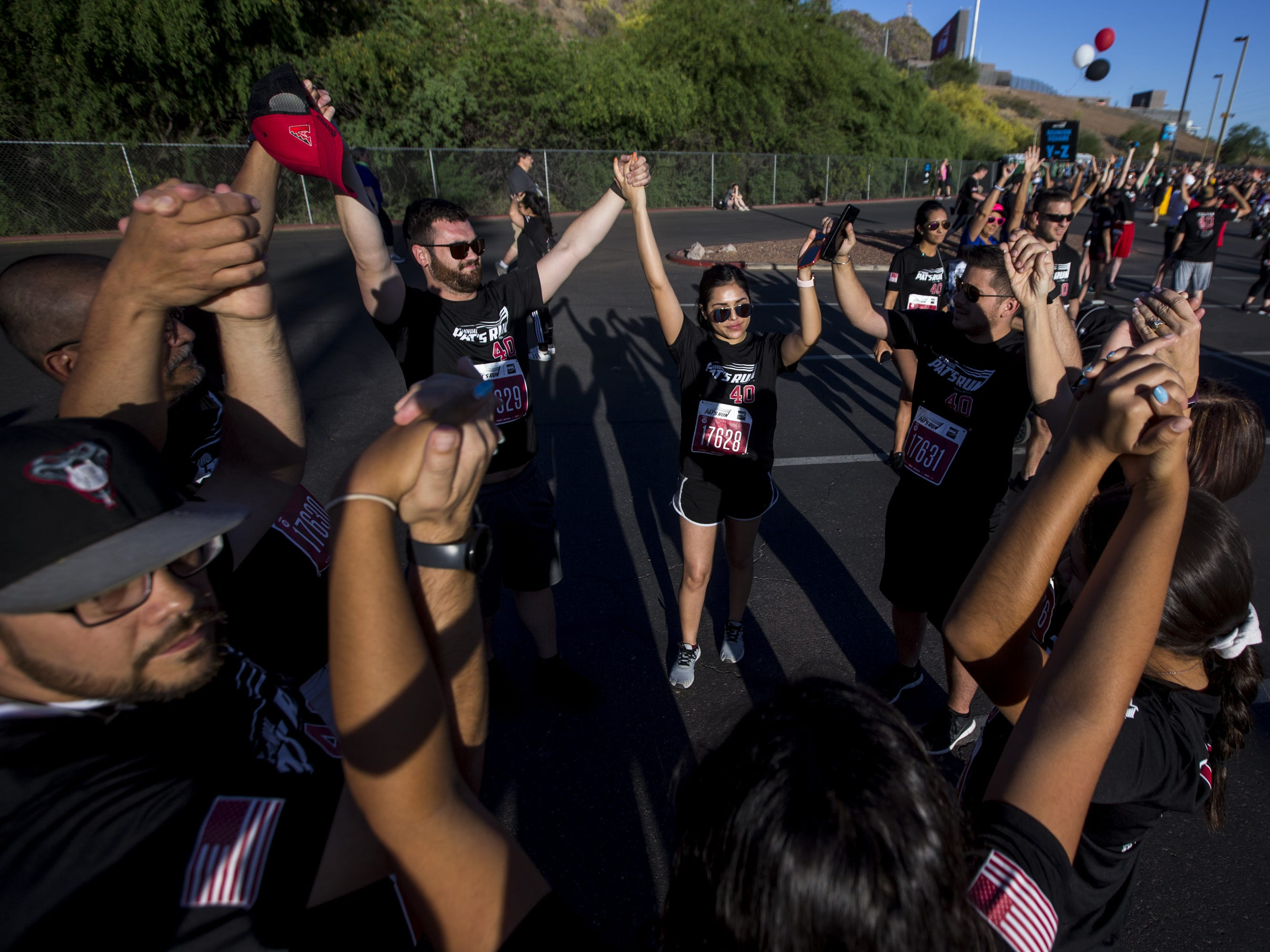 Participants raise their arms after a moment of silence before the 15th Annual Pat's Run on Saturday, April 27, 2019, in Tempe, Ariz.
