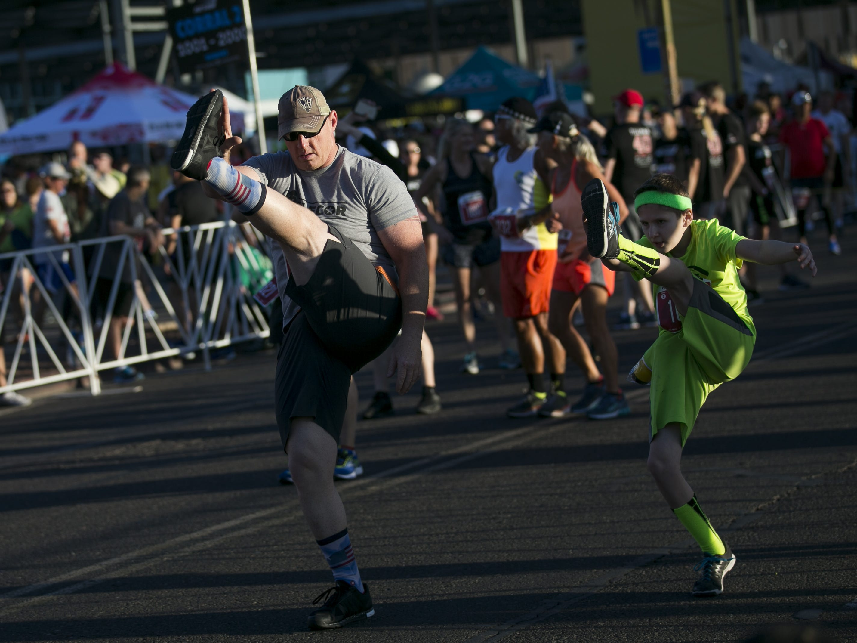 Runners stretch before participating in Pat's Run in Tempe on April 27, 2019.