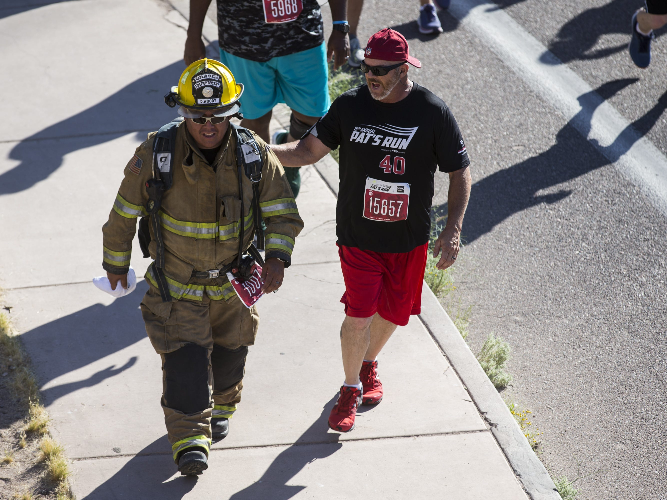 A participant encourages a man walking in firefighting gear during the 15th Annual Pat's Run on Saturday, April 27, 2019, in Tempe, Ariz.