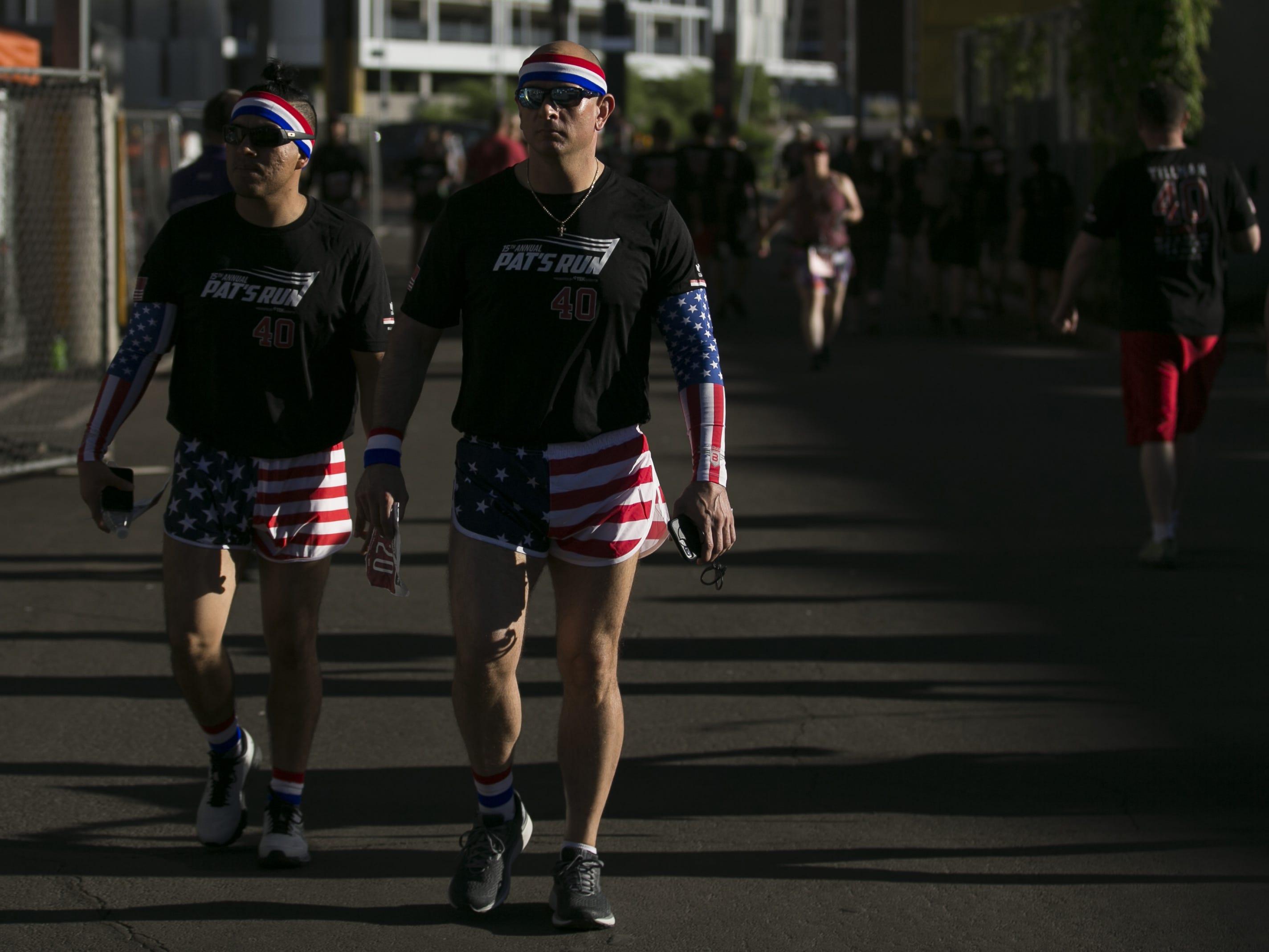 Dionicio Jaramillo (left) and Mike Hennessy (right) walk past Pat's Run 2019 in Tempe on April 27, 2019.