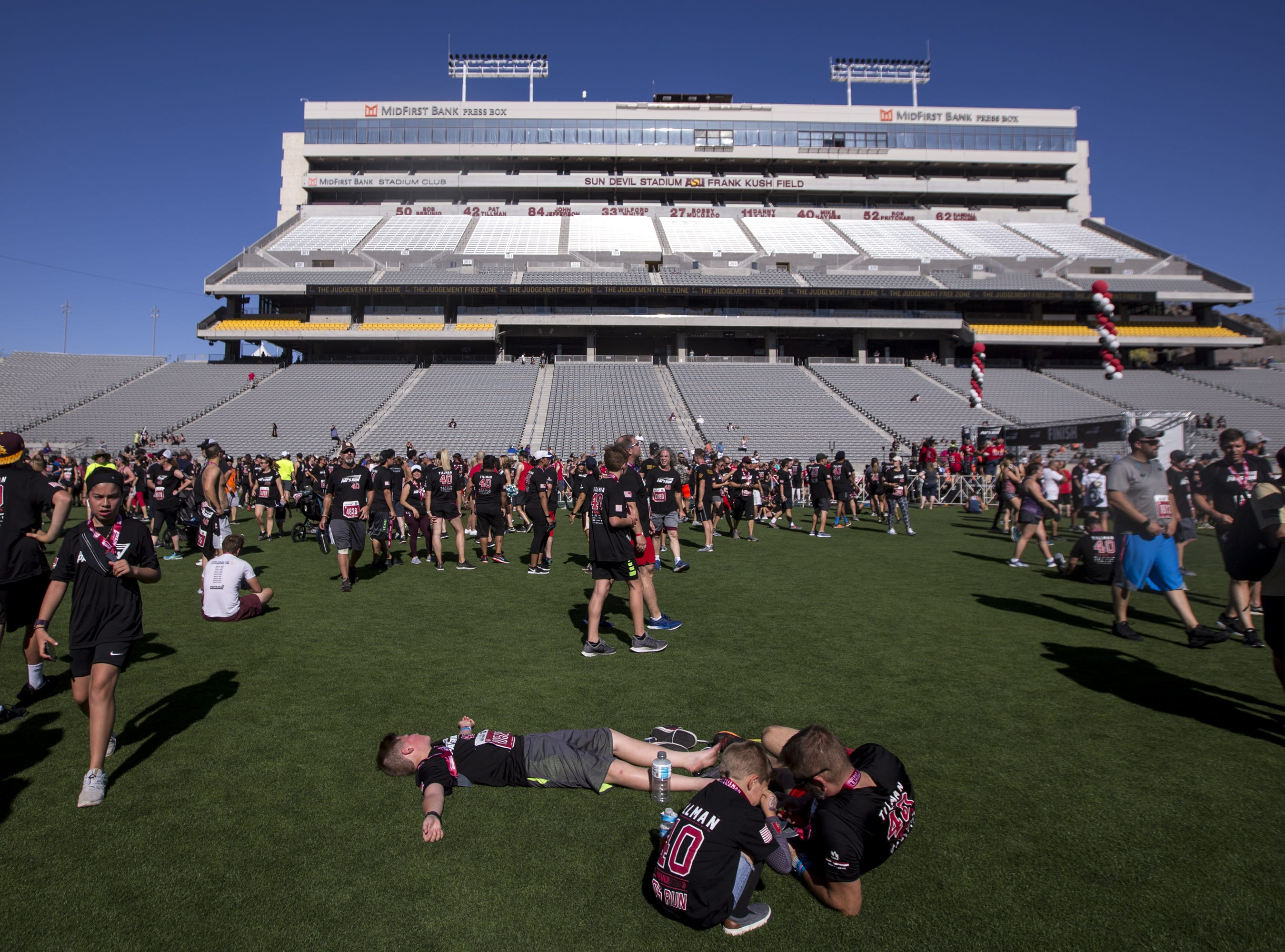 Participants rest on the field at Sun Devil Stadium after the 15th Annual Pat's Run on Saturday, April 27, 2019, in Tempe, Ariz.