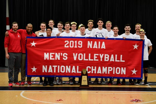 Mesa coach and Benedictine College volleyball coach Ray Lewis with his team's NAIA championship banner