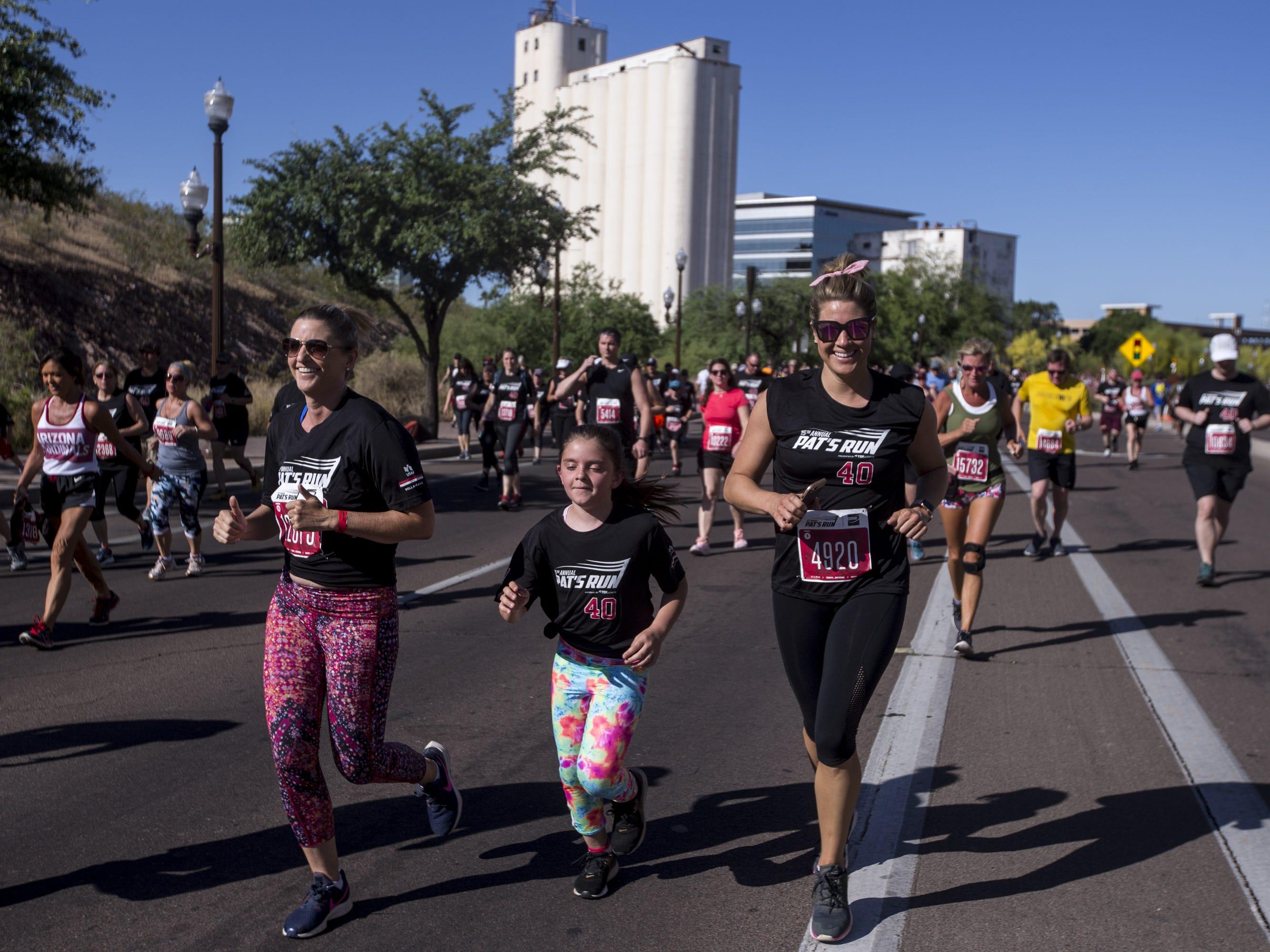 Participants run toward Sun Devil Stadium on Rio Salado Parkway during the 15th Annual Pat's Run on Saturday, April 27, 2019, in Tempe, Ariz.