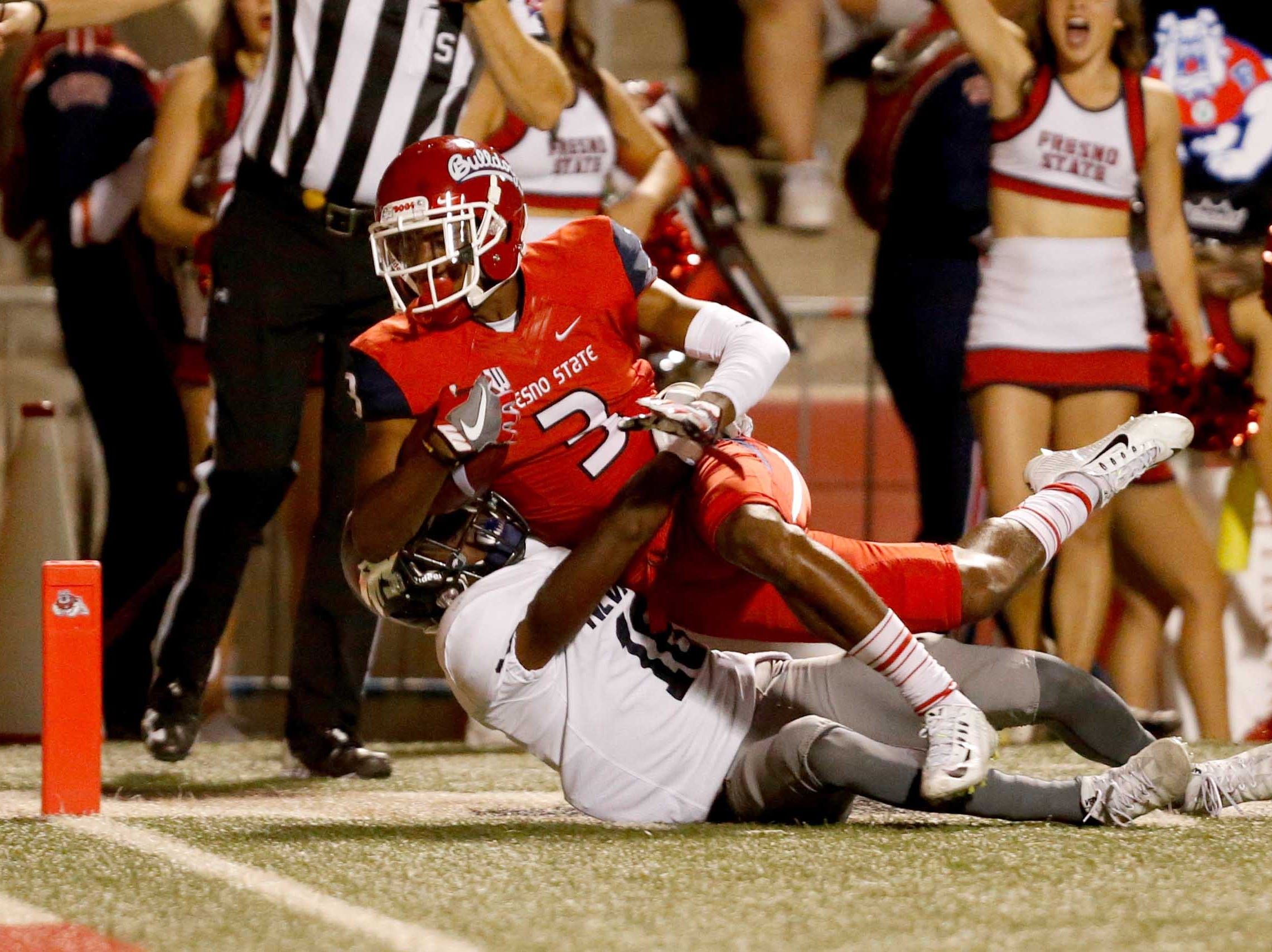 Fresno State receiver KeeSean Johnson (3) falls over Nevada defensive back Elijah Moody (18) for a touchdown during a game at Bulldog Stadium.