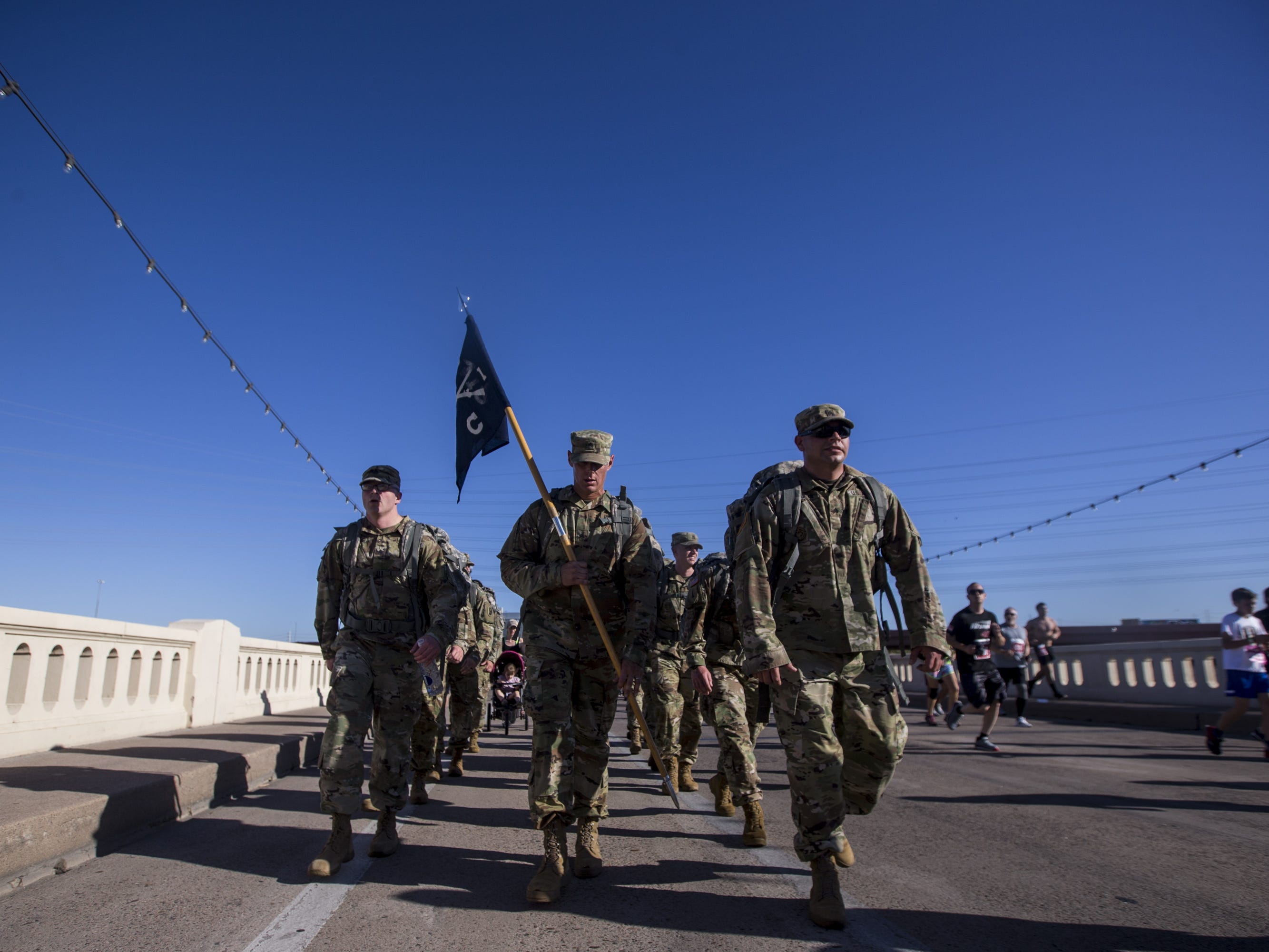 Military personnel walk across the Mill Avenue bridge during the 15th Annual Pat's Run on Saturday, April 27, 2019, in Tempe, Ariz.