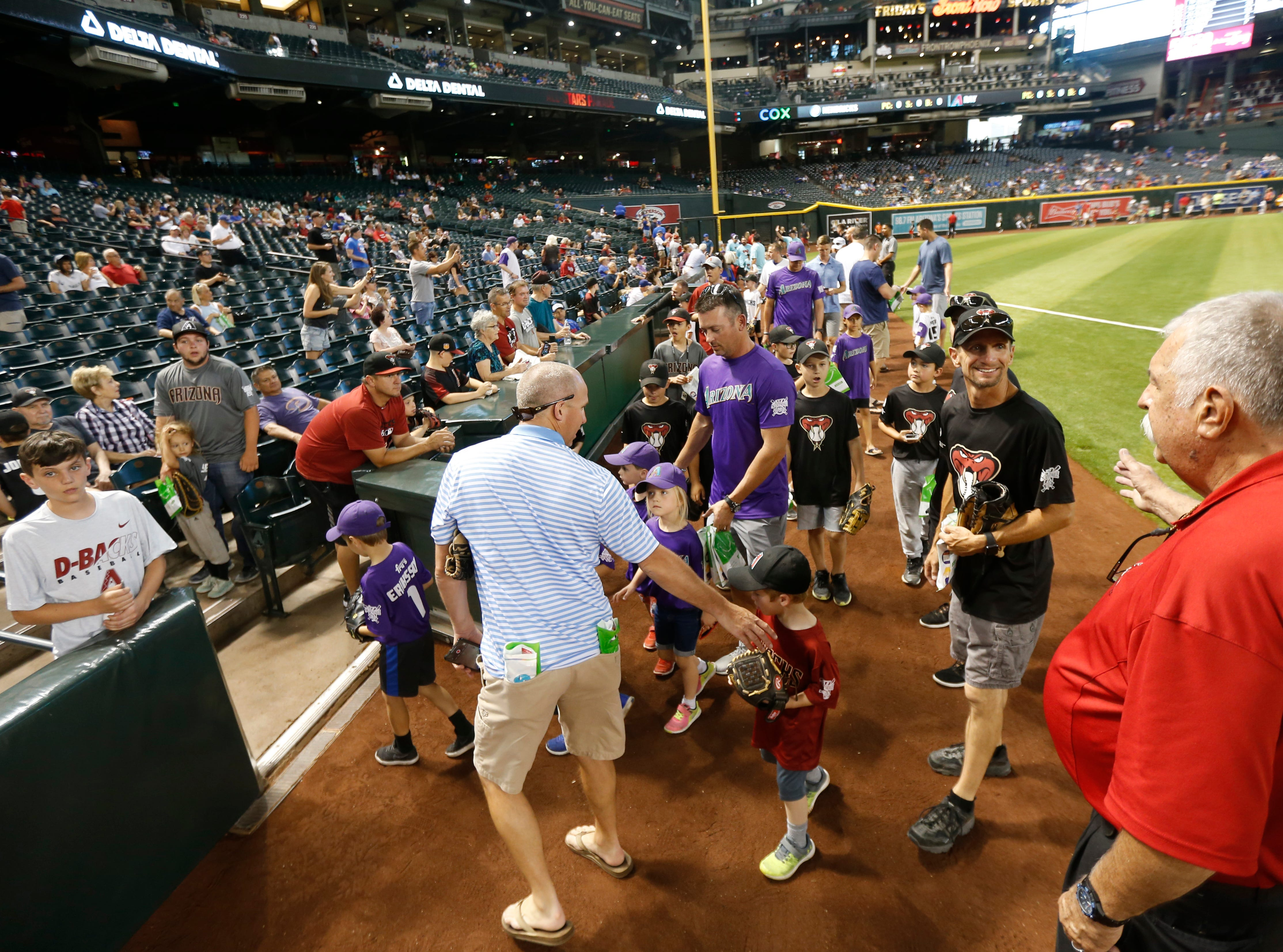Fans make their way off the field after walking the dirt in the outfield during the Arizona All-Stars Parade before a Cubs vs. Diamondbacks game at Chase Field in Phoenix, Ariz. on April 26, 2019.