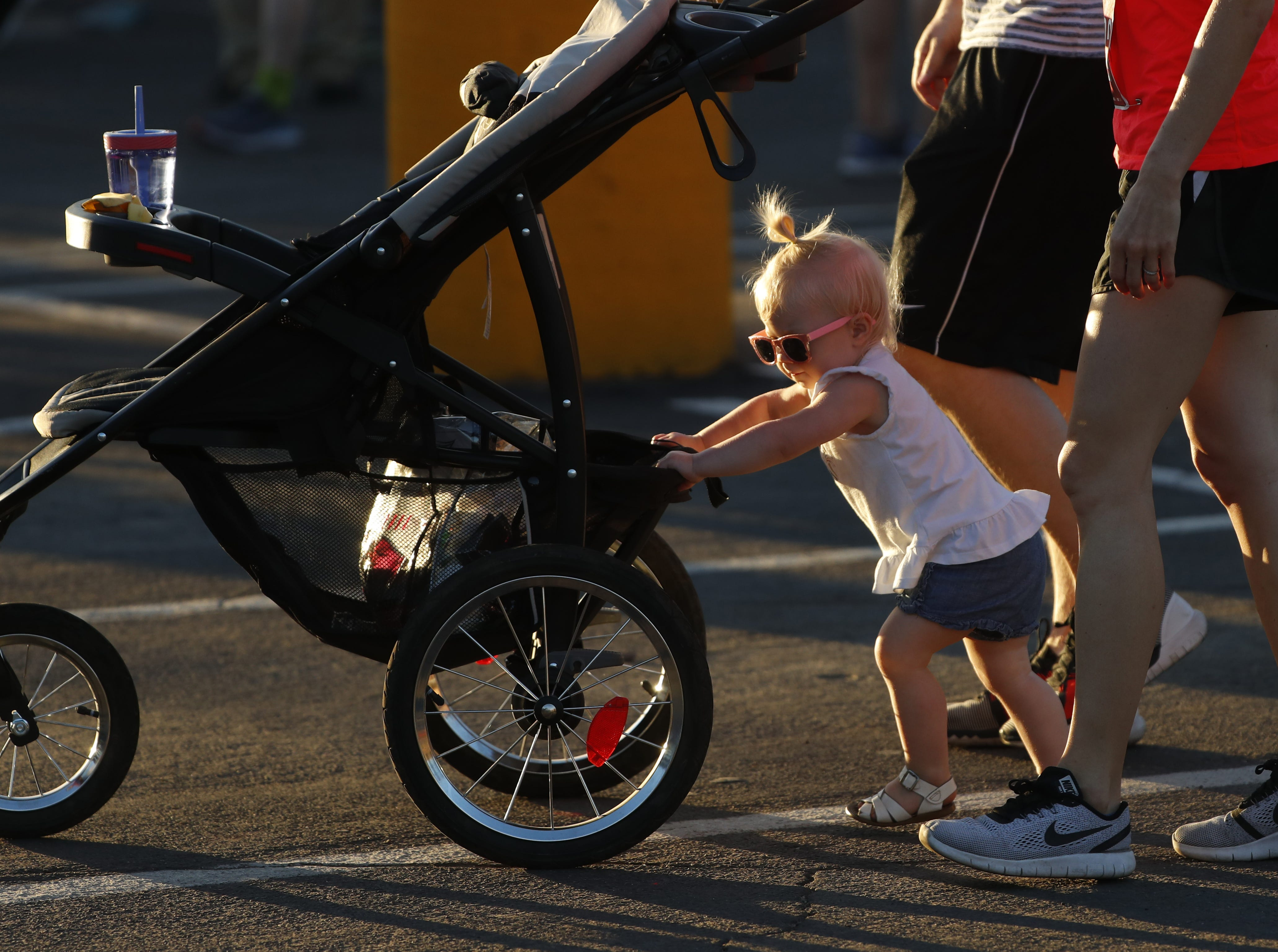 A young walker helps her parents push her stroller on the way to the starting line during Pat's Run 2019 in Tempe, Ariz. on April 27, 2019.