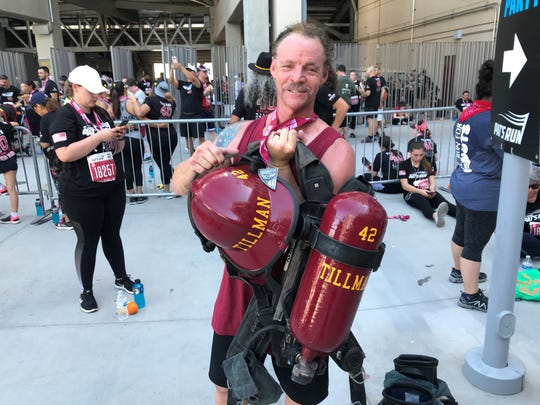 David Kerr, a firefighter with the Phoenix Fire Department, shows off some of the gear he wore while walking Pat's Run on April 27, 2019.