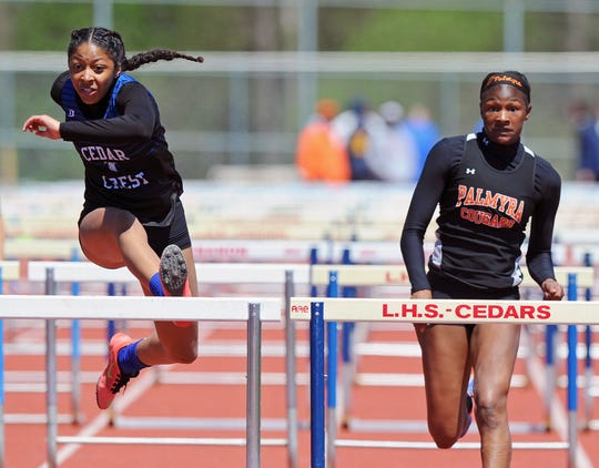 Cedar Crest's DeAsia Holloman, left, eyes the finish line en route to setting a new county meet record in the 100 high hurdles Saturday. At right is runner-up Maliyah Stough of Palmyra.
