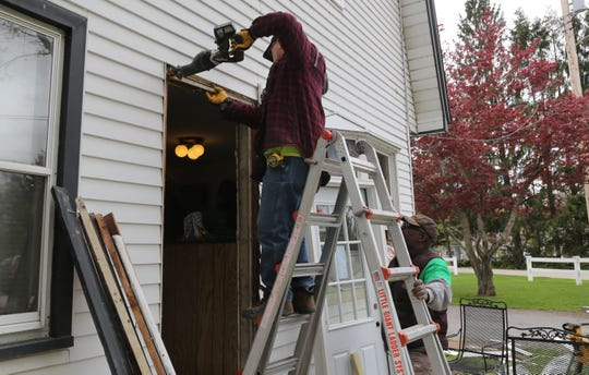 Marc Dennis (right), of Beacon, holds the ladder for Larry Theisen, of Hyde Park, as he works on replacing the front door of Lee Baker's Hillside Lake home. The volunteers were two of 25 who were working on the home.