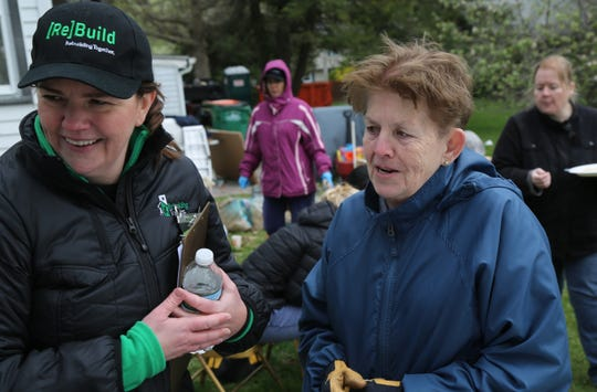 Lee Baker (right) shares a moment with Rebuilding Together Executive Director Christina Boryk on Saturday outside of her Hillside Lake home. Rebuilding Together fixed up six homes including Lee's on Saturday for National Rebuilding Day.