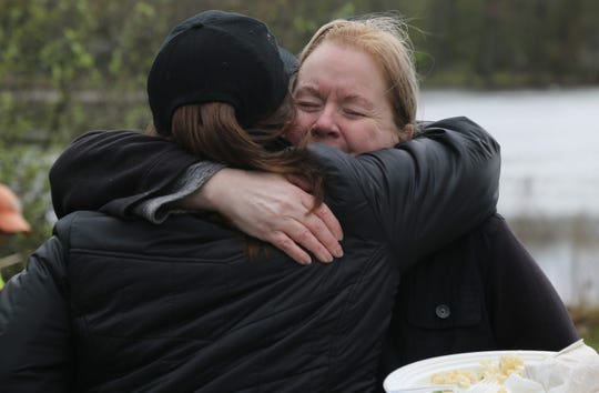 Annmarie Baker (right) hugs Rebuilding Together Executive Director Christina Boryk outside of her mother's Hillside Lake home on Saturday. She said the home has kept family traditions alive.