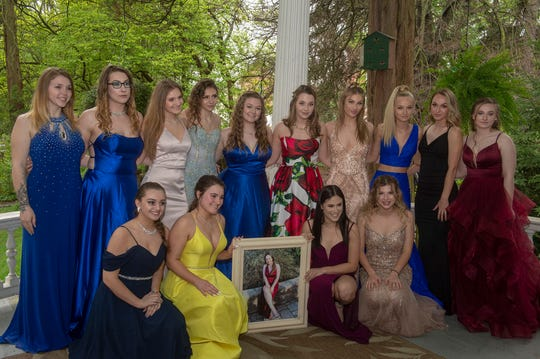 Friends hold a portrait of Masey Dacheux to continue the tradition of getting photos taken and going to Northeastern homecoming dances and prom in a group. They met at Emig Mansion Bed and Breakfast Friday, April 26, 2019 before the prom.