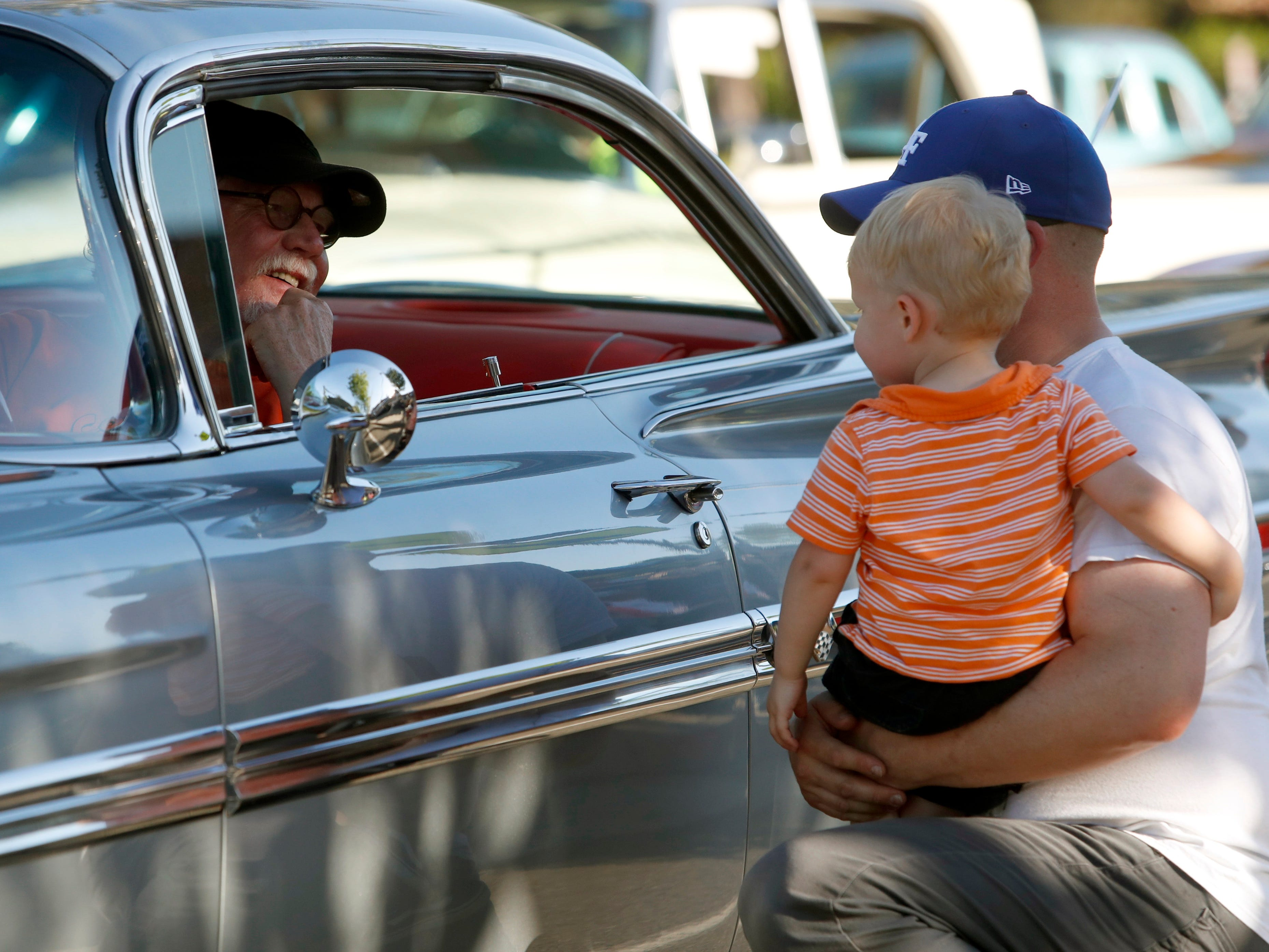 Devon Smith of Redding, right, holds his 20-month-old son Beckett while he chats with a driver before the Friday Nite Cruise gets underway on Hilltop Drive as part of the 2019 Kool April Nites classic car show.