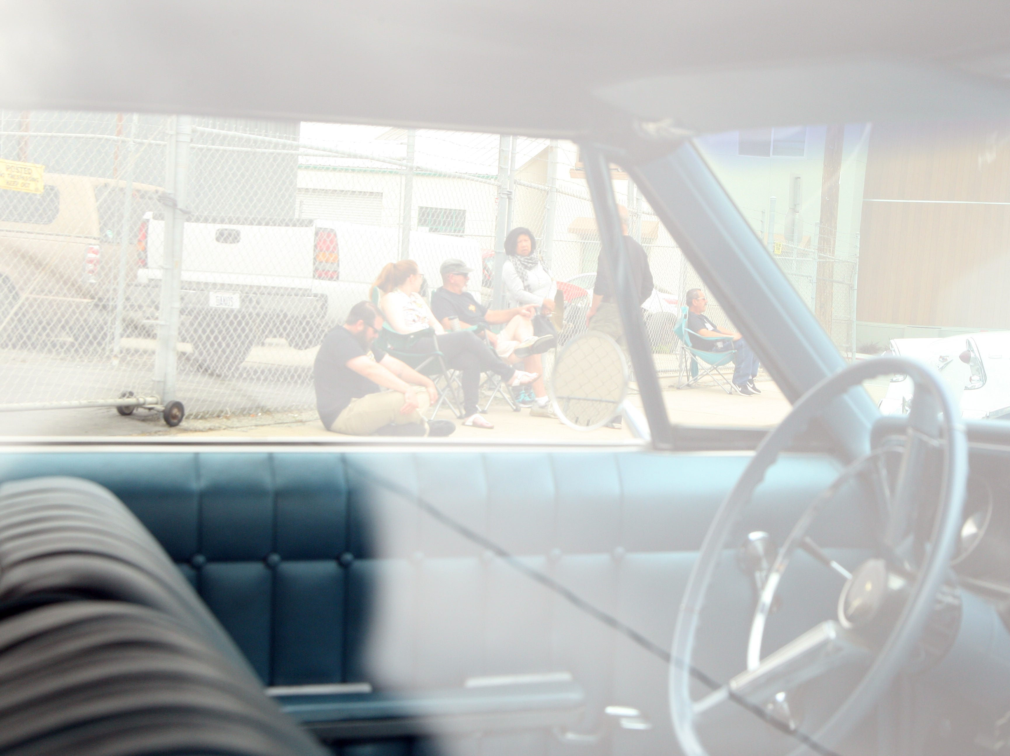 A group of car owners perches on the sidewalk, ready to talk to anyone interested in their classic cars. April 27, 2019.