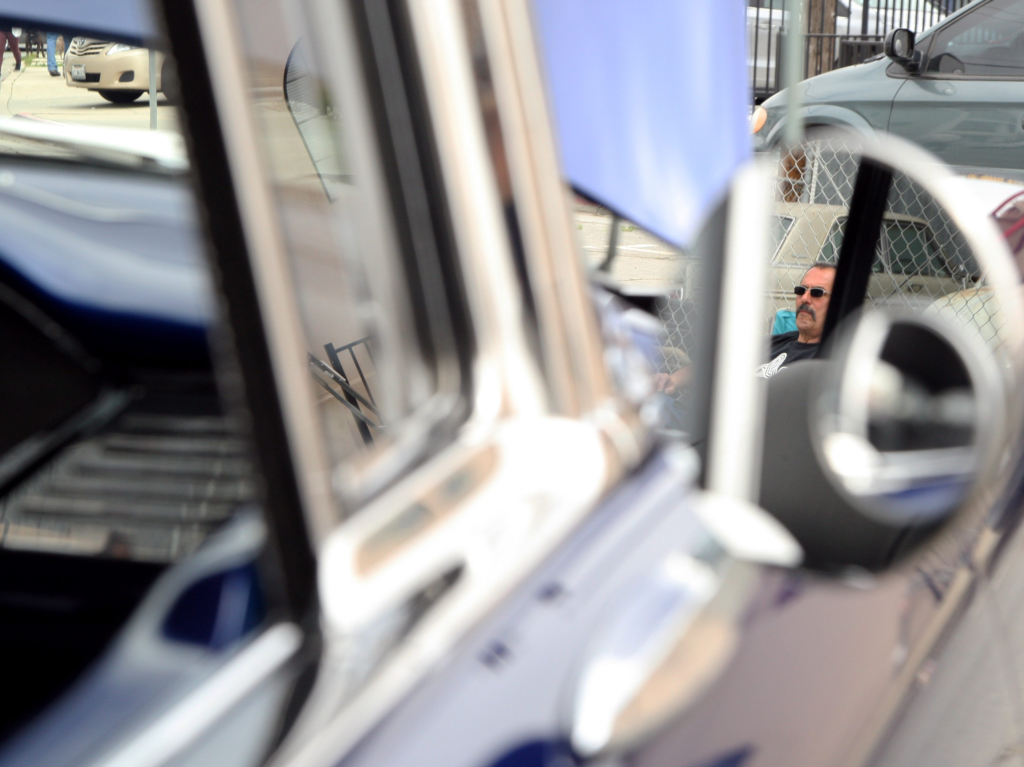 Robert Barba is pictured in the reflection in the sideview mirror of a classic car. This is his first year attending the Annual Asian Festival in Salinas's Historic Chinatown, but he is a regular at car shows. He owns a 1966 Chevy Impala, which he brought along Saturday. April 27, 2019.