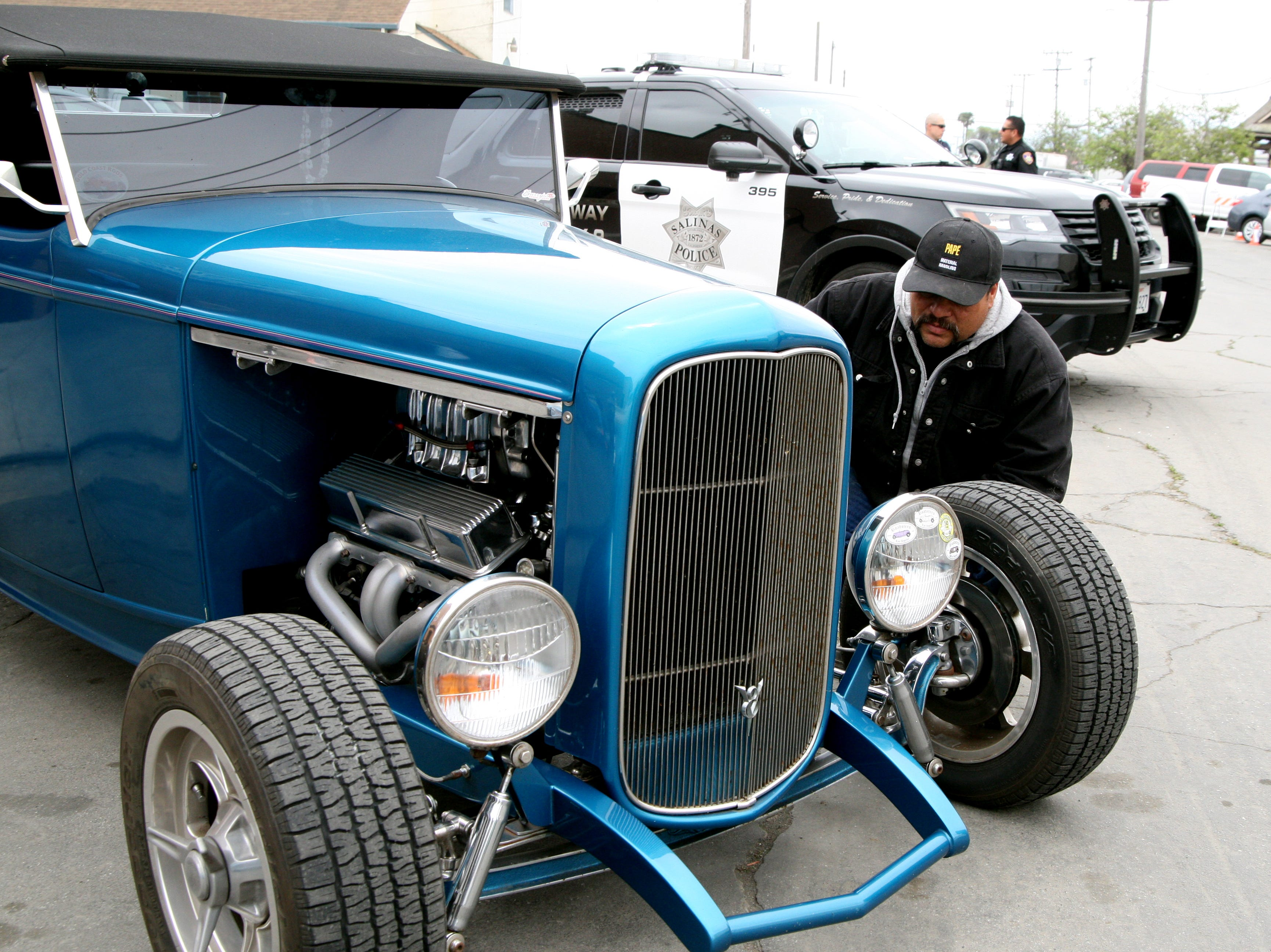 A festival attendee examines a 1932 classic car, painted cerulean blue. April 27, 2019.