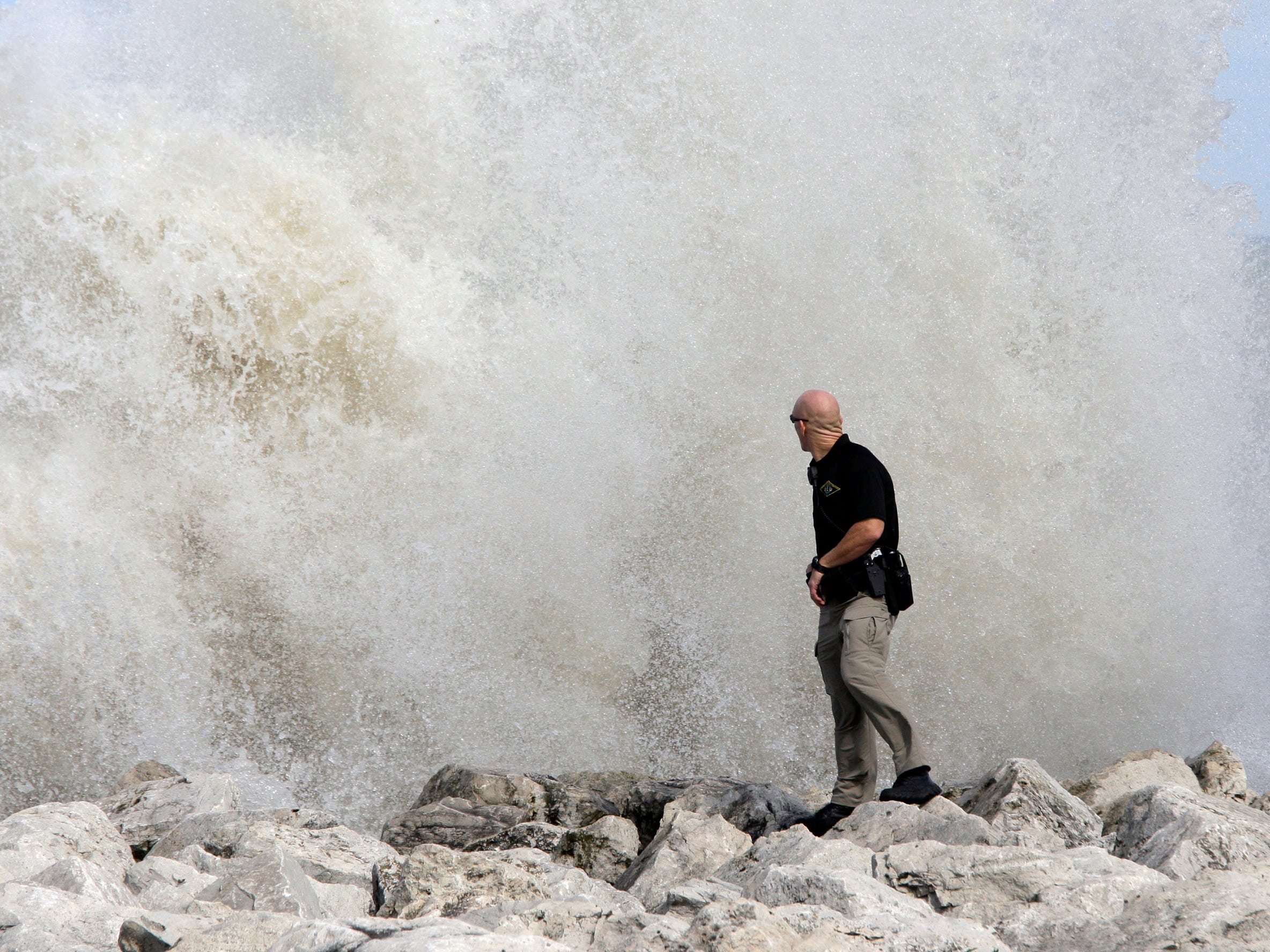 A law enforcement official is small compared to the huge wave at North Pier on Aug. 10, 2012, in Sheboygan, Wis., at the scene where people were swept off the pier.  FILE PHOTO